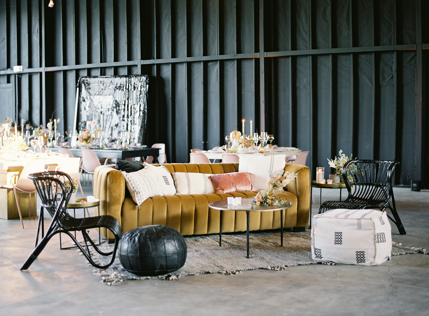 lounge space with bold colored couches and black wicker chairs