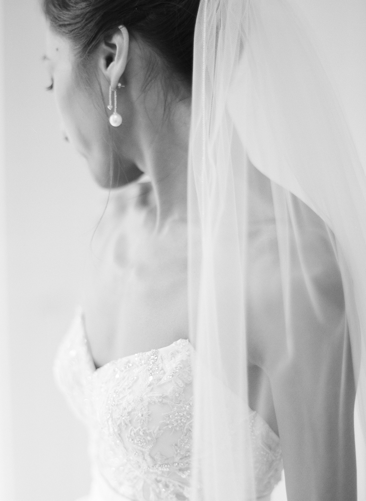 Bride wearing a simple gold hairpin and pearl drop earrings