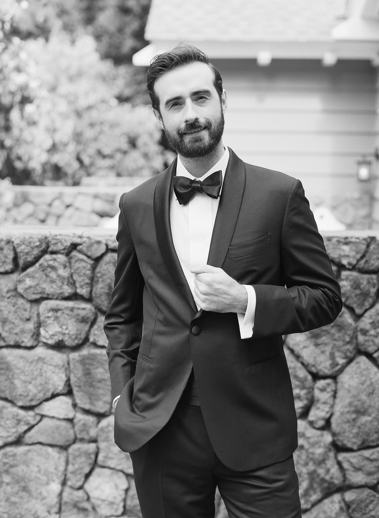 Groom in Brioni tuxedo with a shawl collar, a custom tuxedo shirt, a black bow tie, and a cummerbund