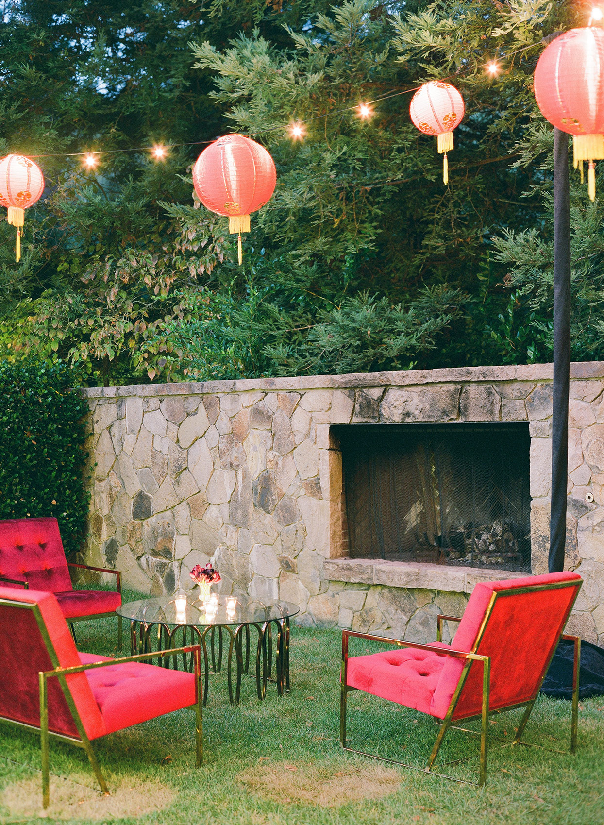 Wedding lounge area with capiz lanterns, red chairs, and fireplace