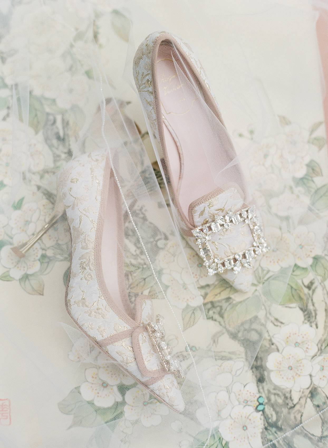 Bride's Roger Vivier pumps with a floral fabric, nude trim, Swarovski crystal buckle, and a comma heel