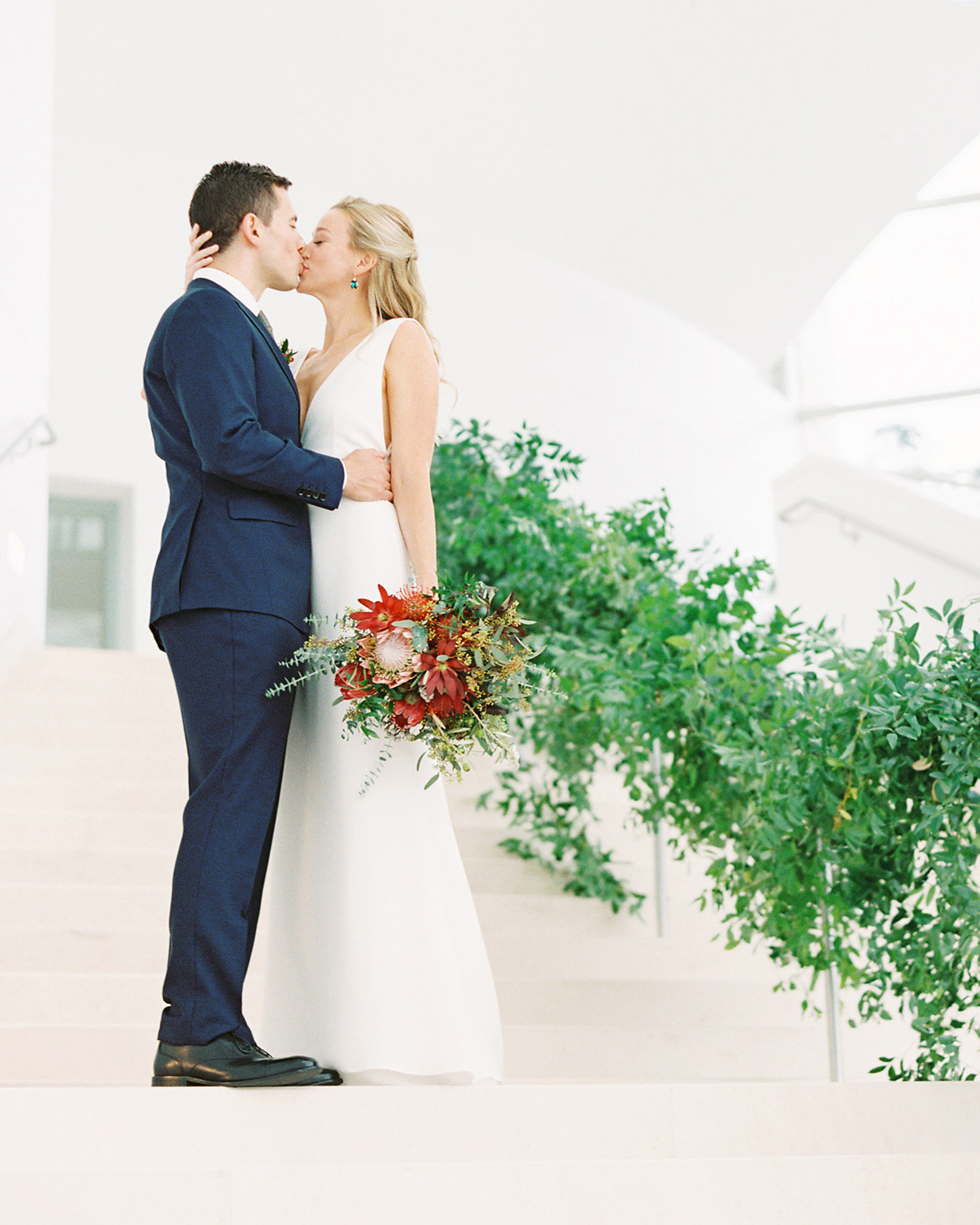bride and groom share kiss on greenery covered stairway