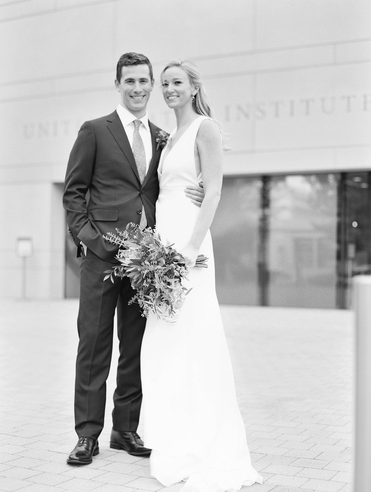 bride and groom smile for portrait shot outside