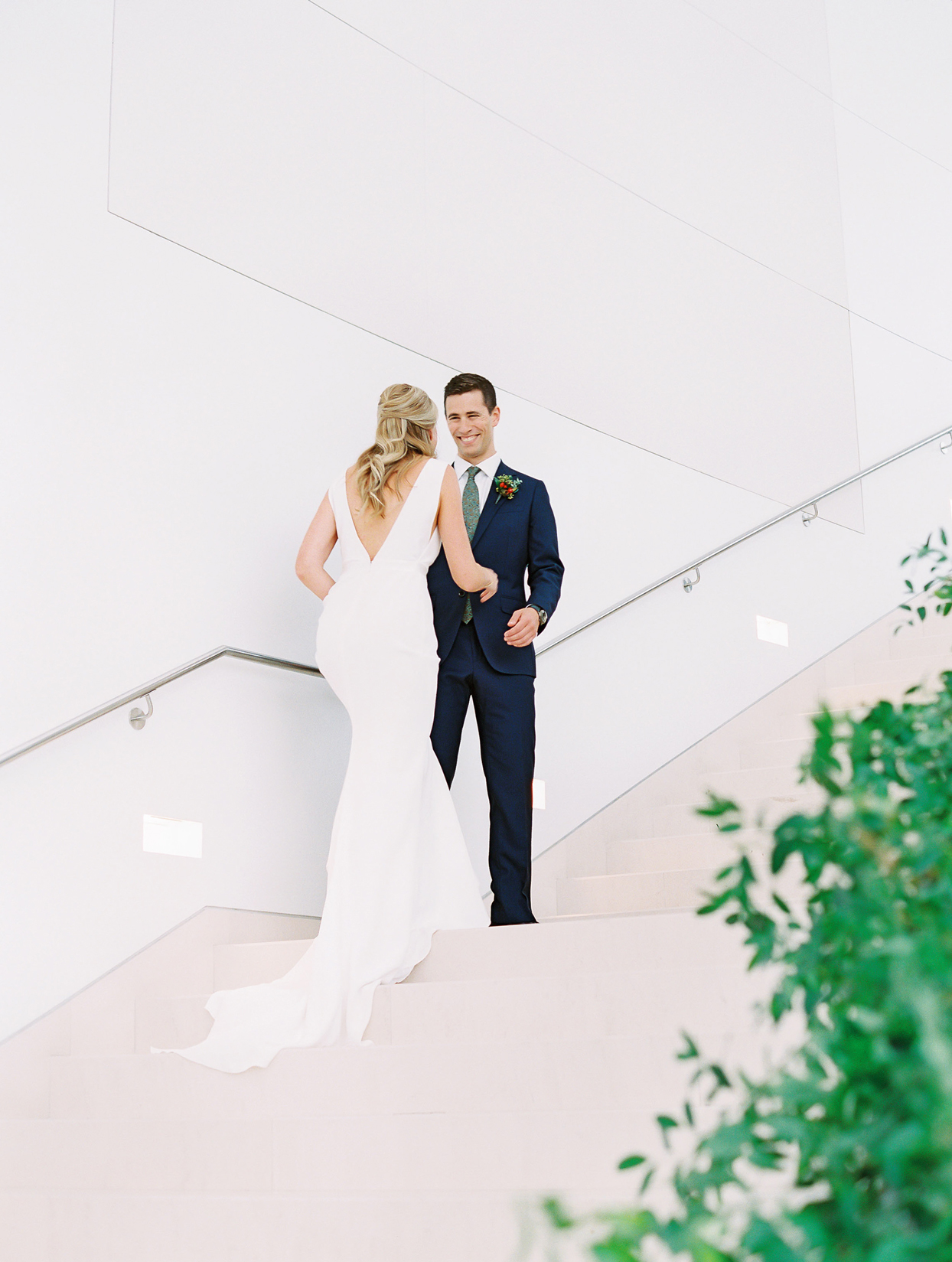 groom smiles at bride during first look on staircase