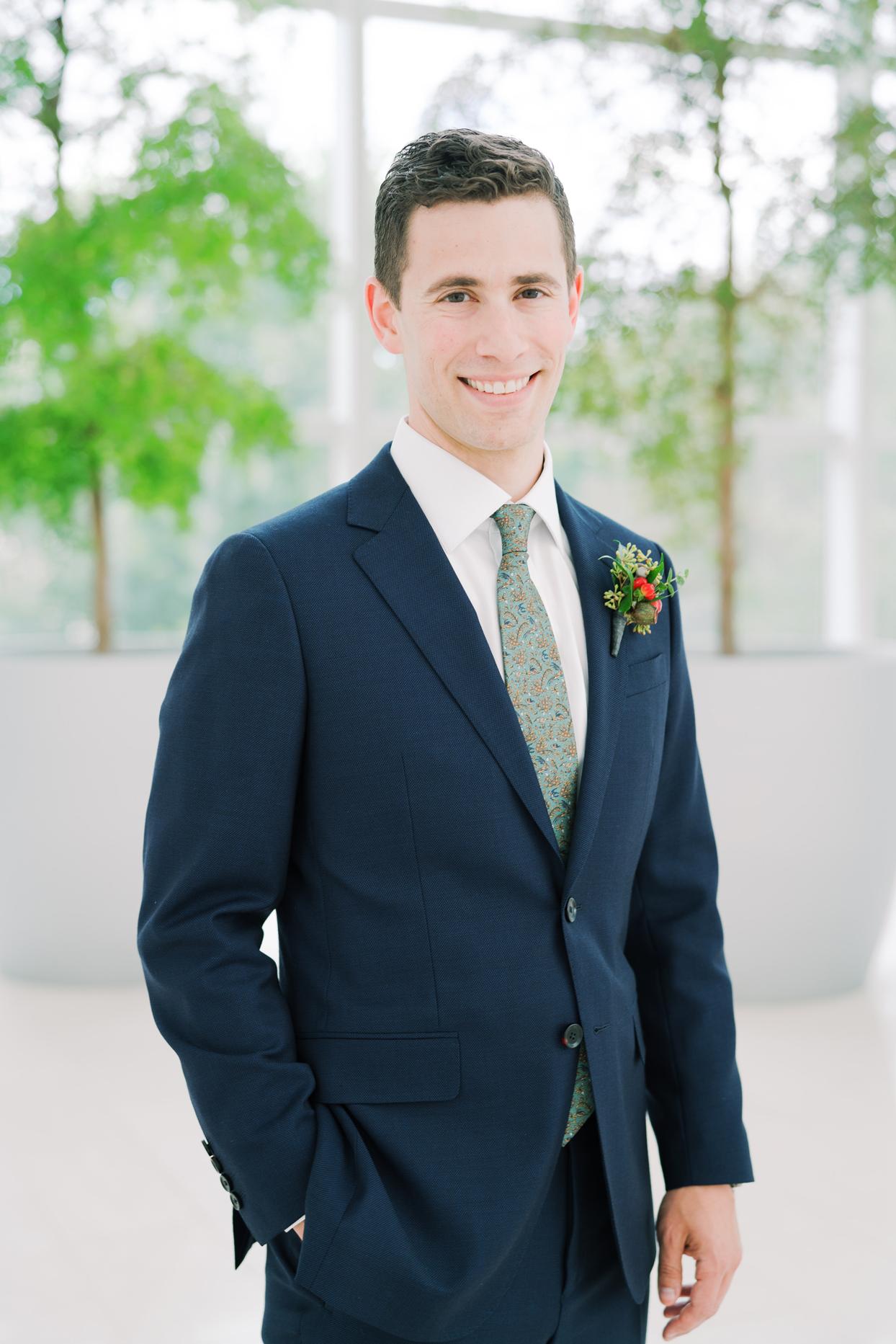 groom wearing navy blue suit with green printed tie