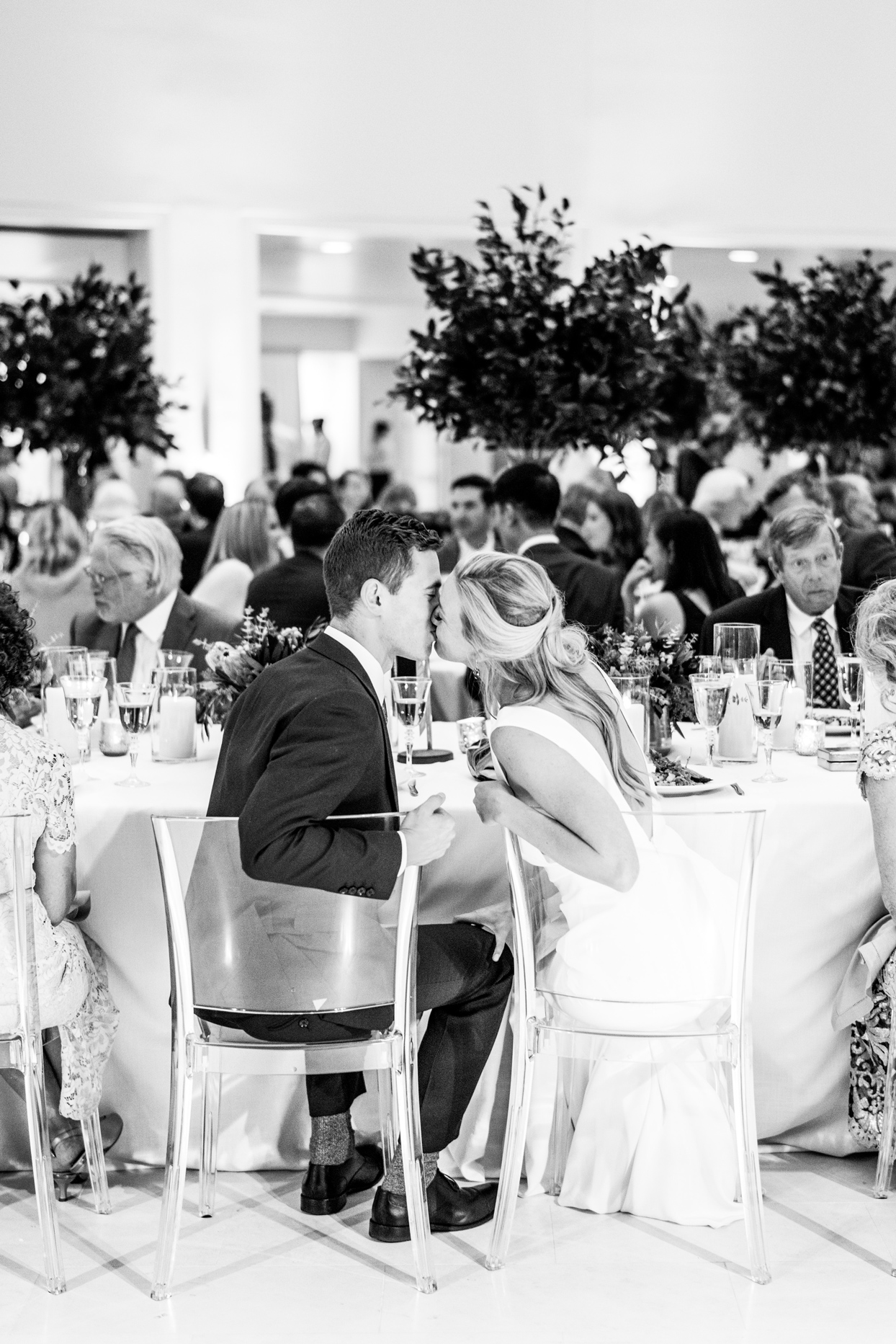 bride and groom share kiss at reception table