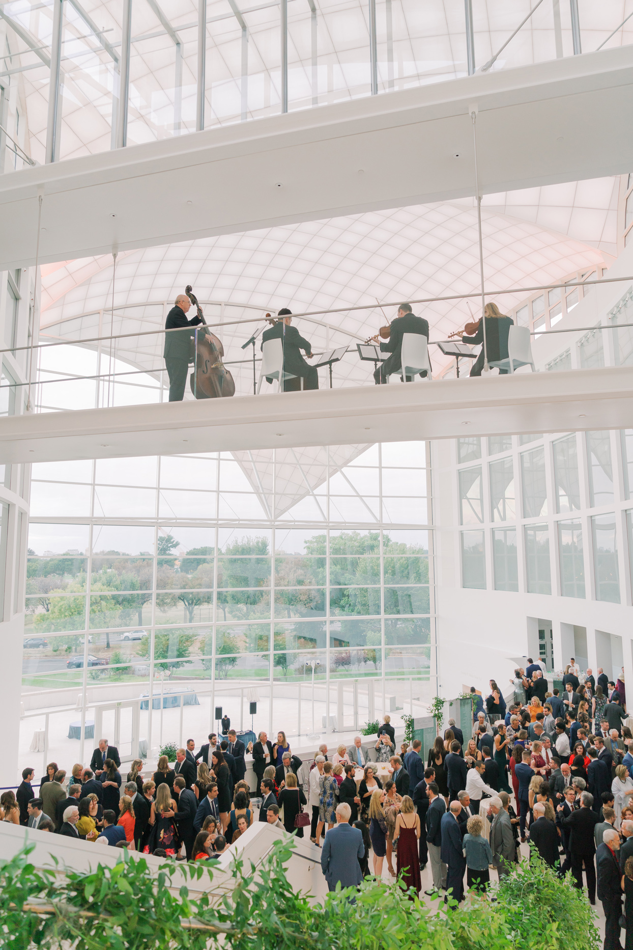 string band playing overhead of guests during wedding reception