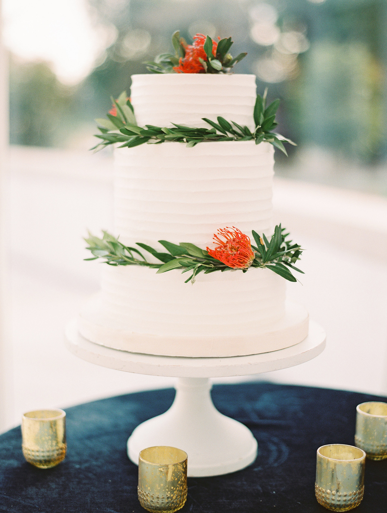 three tiered white frosted wedding cake with greenery and red floral accent