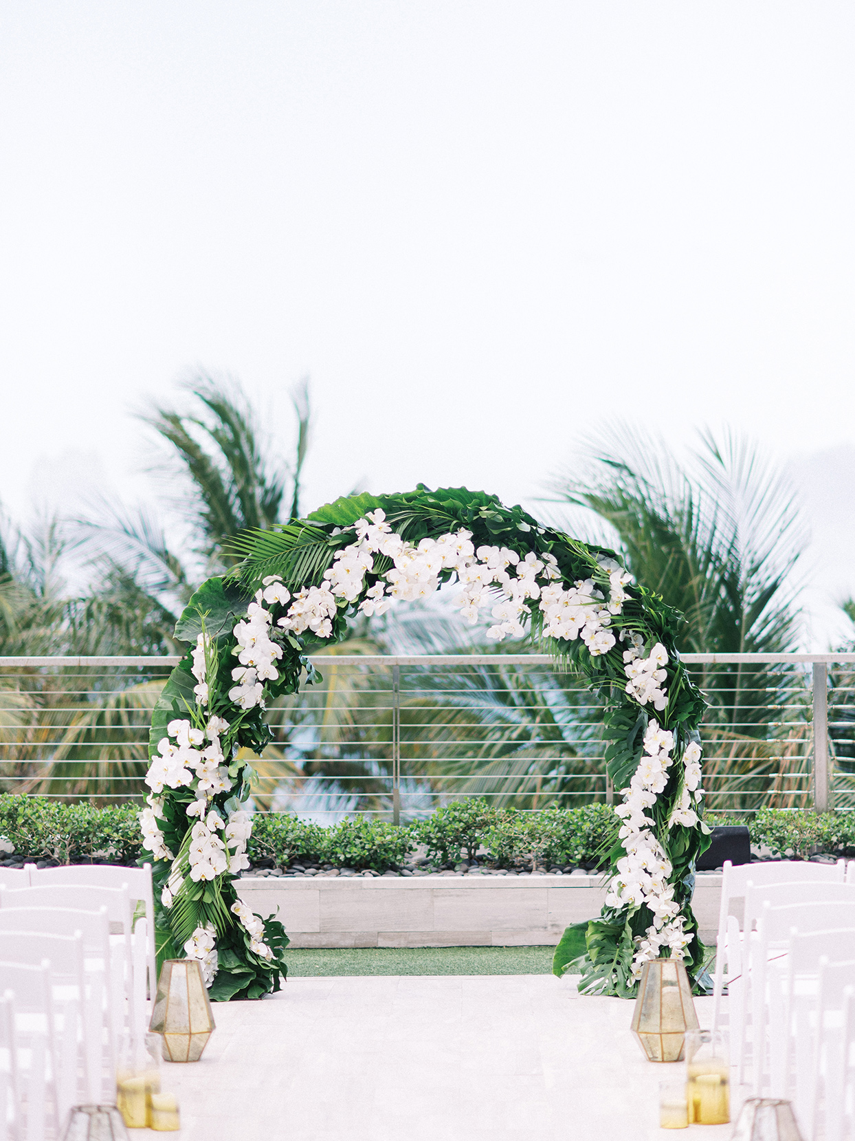 Wedding arch with green foliage and accents of phalaenopsis orchids