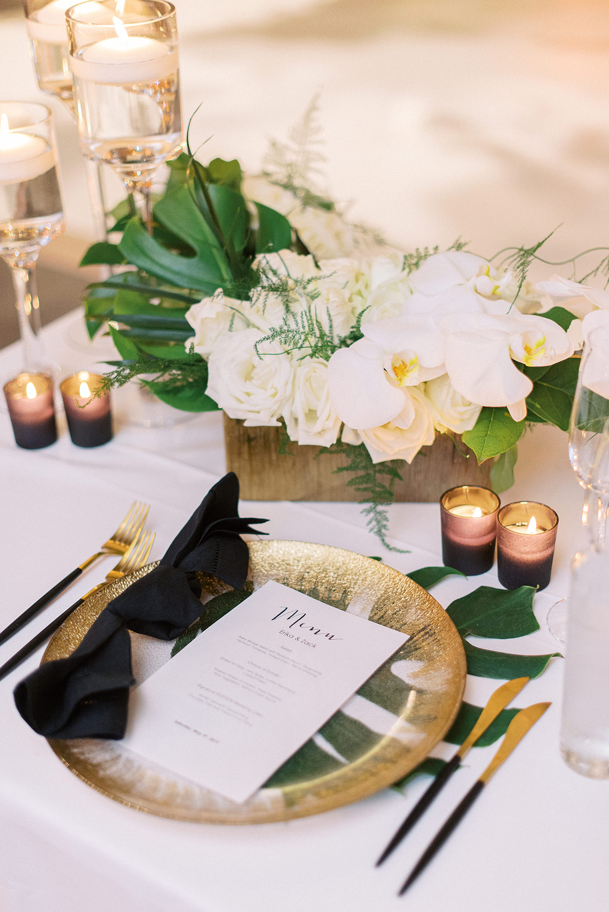 Wedding place setting with gold chargers, gilded flatware, and black hemstitch napkins