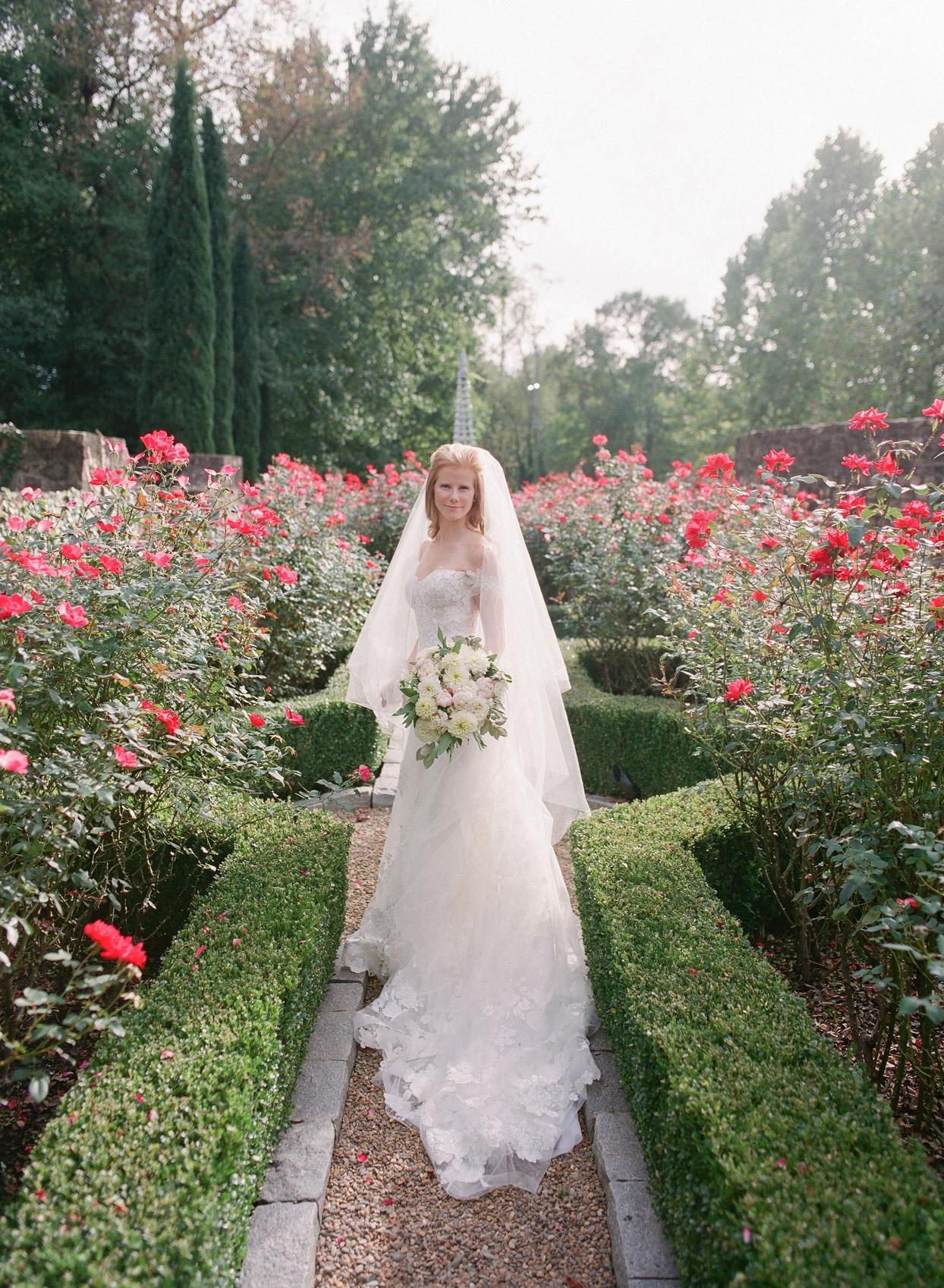 bride outside in flower garden wearing dress and veil