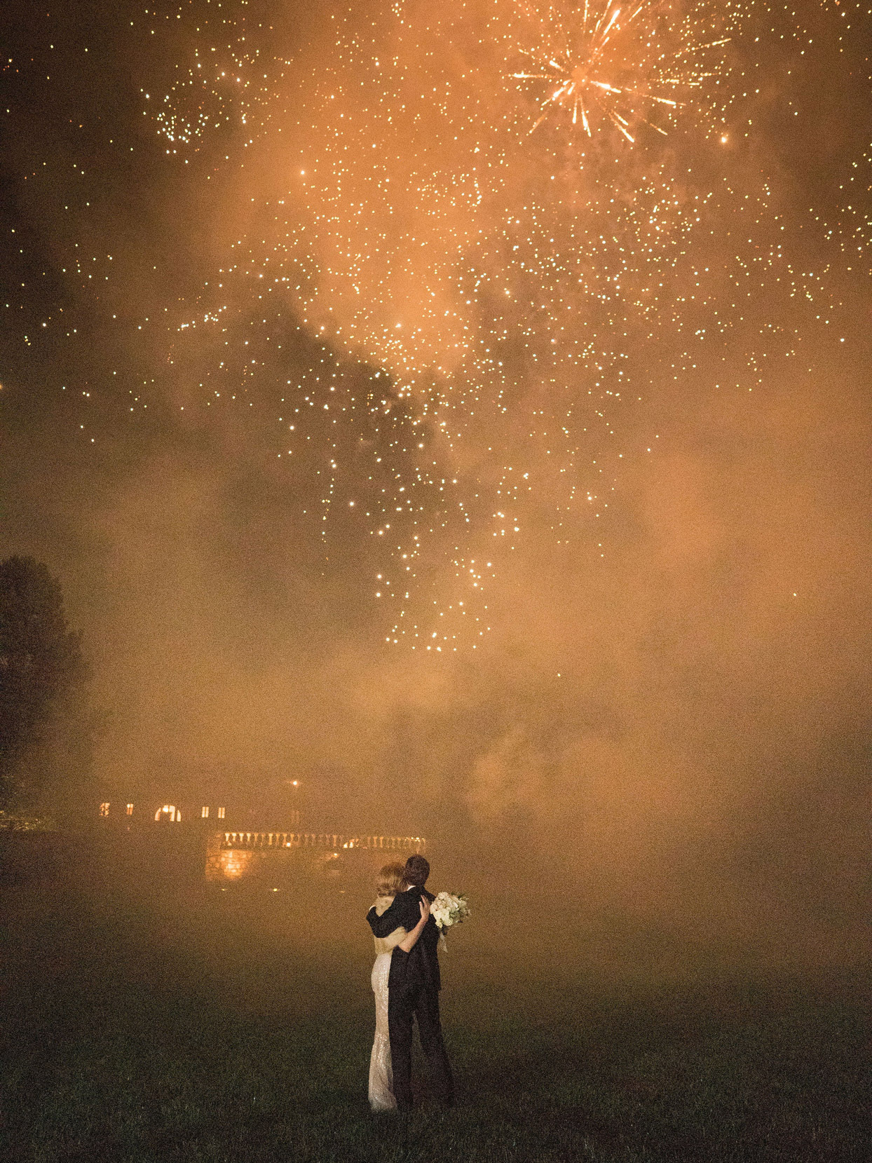 bride and groom standing under fireworks filled sky