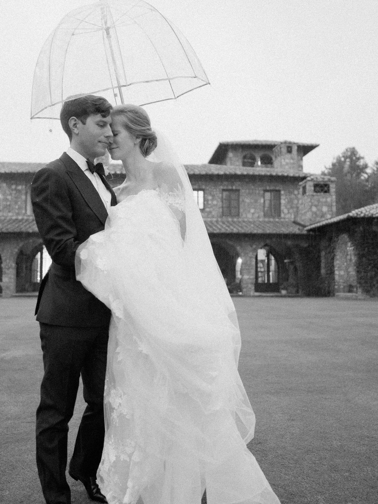bride and groom outside under umbrella