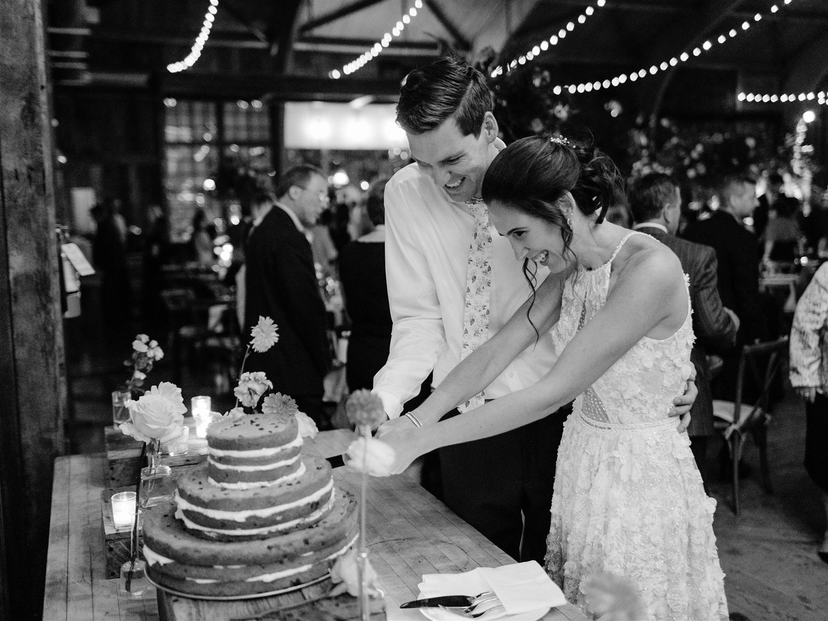 bride and groom smiling while cutting naked cake