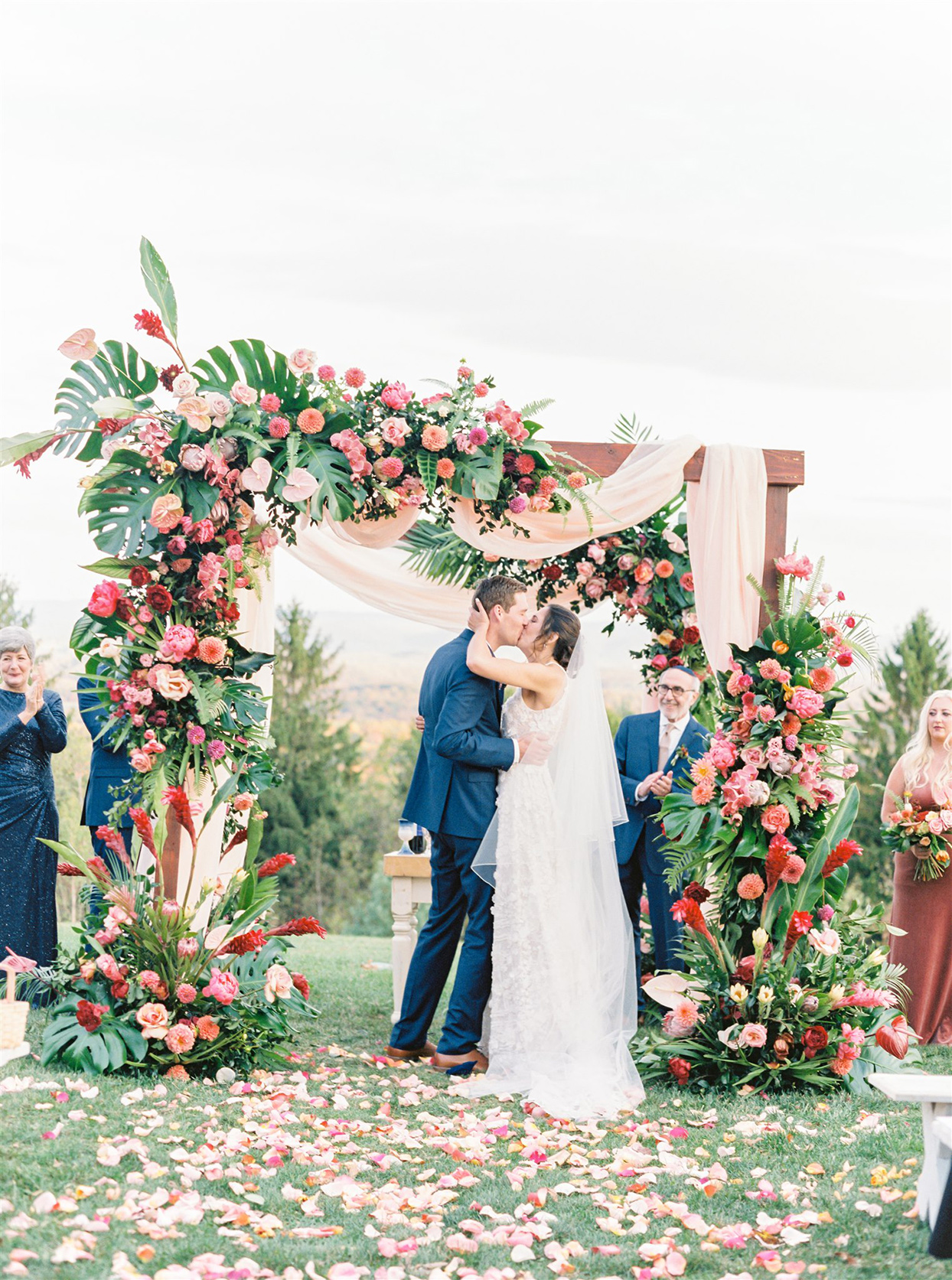 couple kissing under floral arch at outdoor ceremony