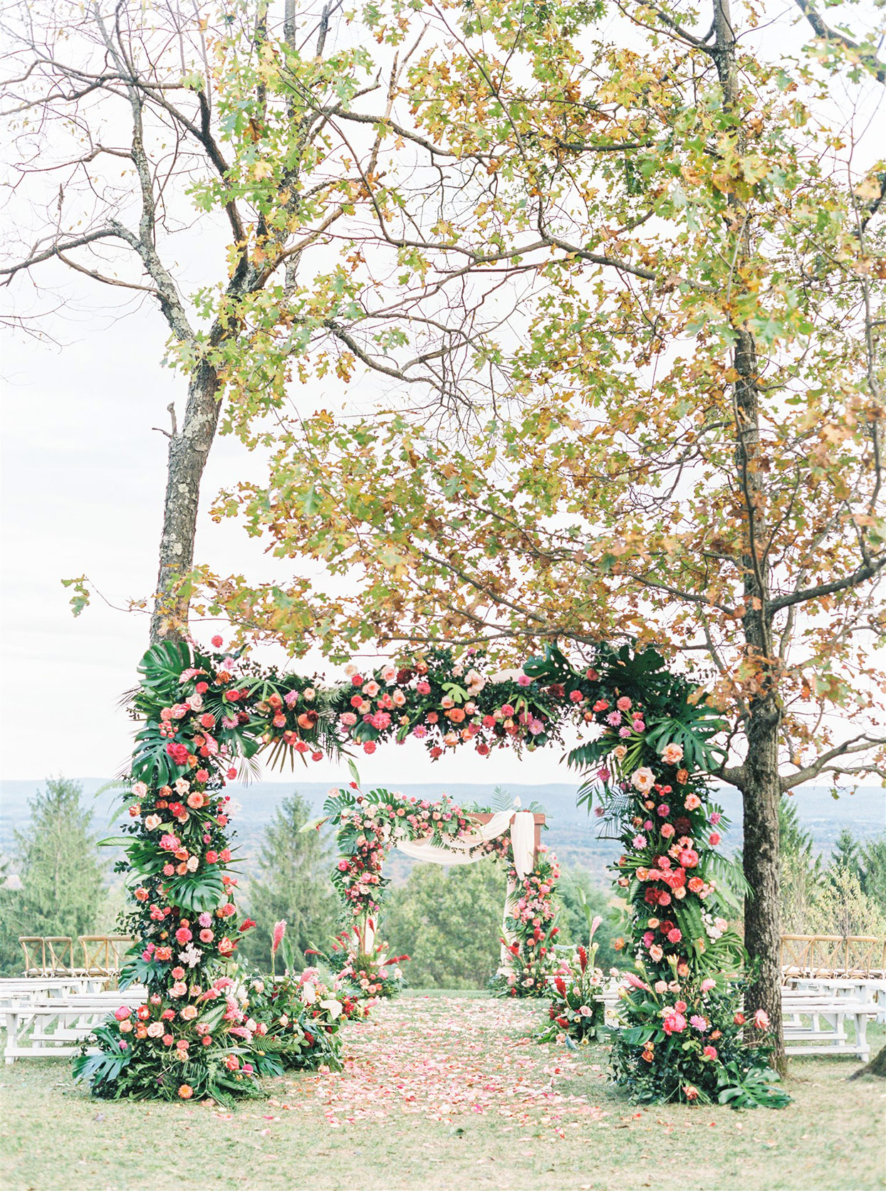 outdoor fall wedding setting with floral arches and petal walkway