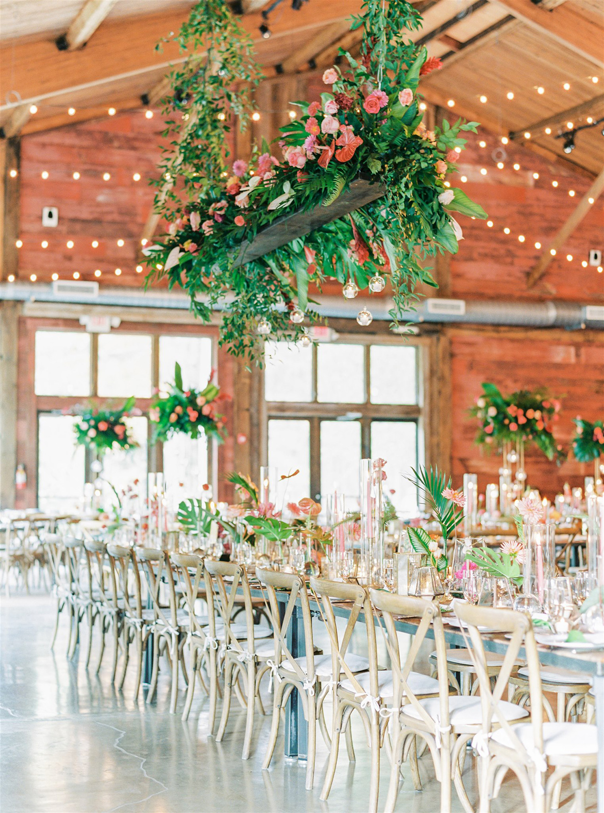 long wooden reception tables with tropical greenery and florals