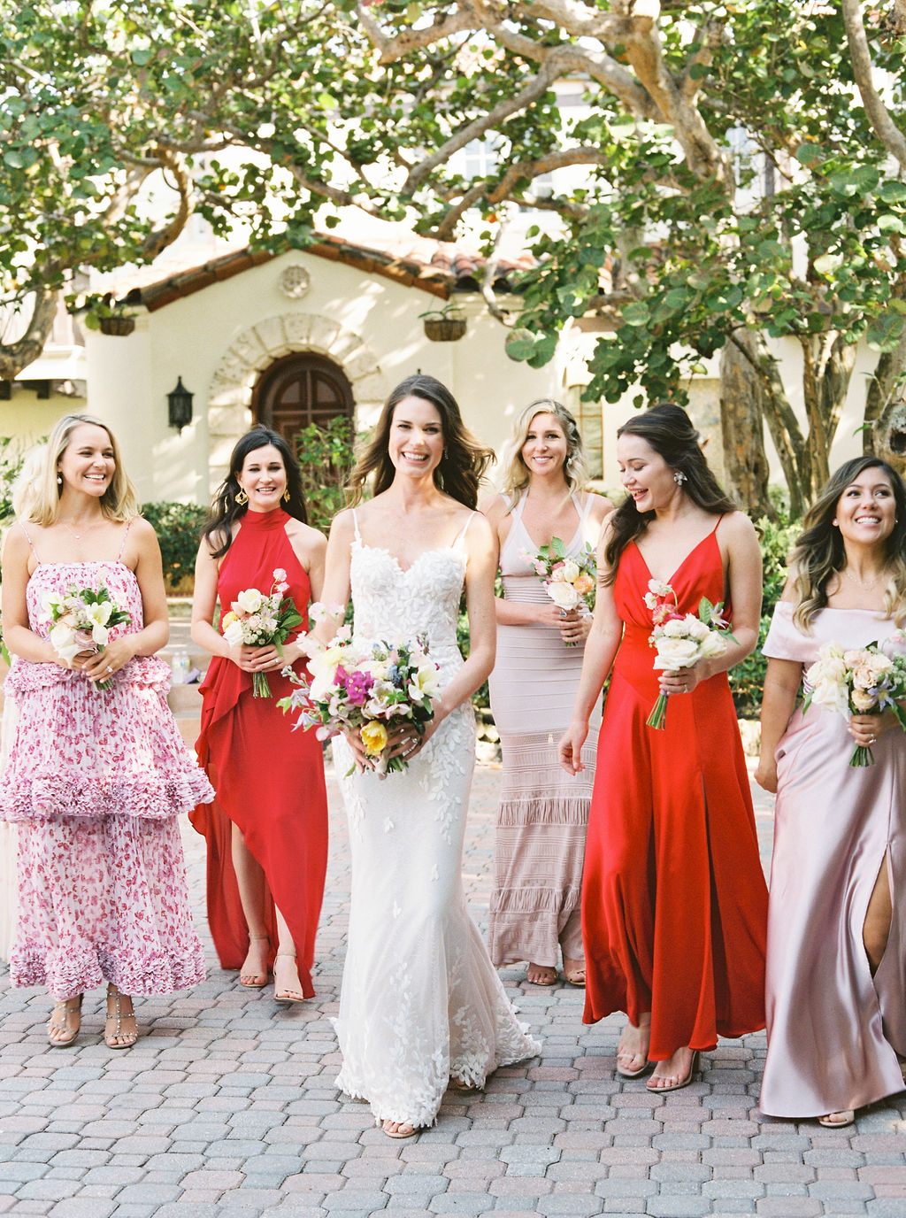 bride and bridesmaids in varied dresses walking along courtyard