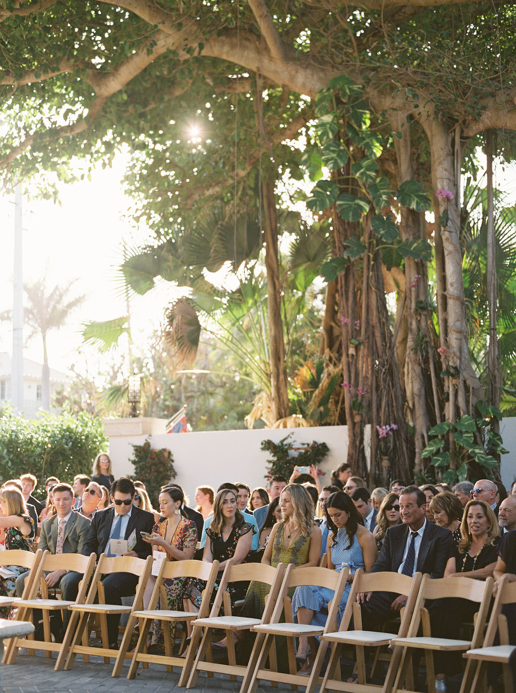 wedding guests sitting in wooden chairs for backyard wedding