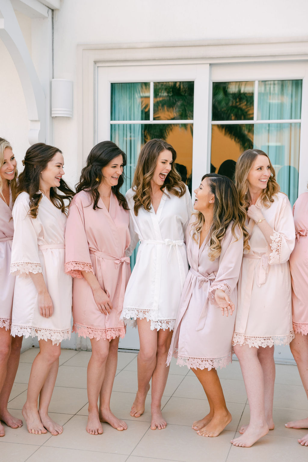 bride and bridesmaids in pastel pink and white dressing gowns