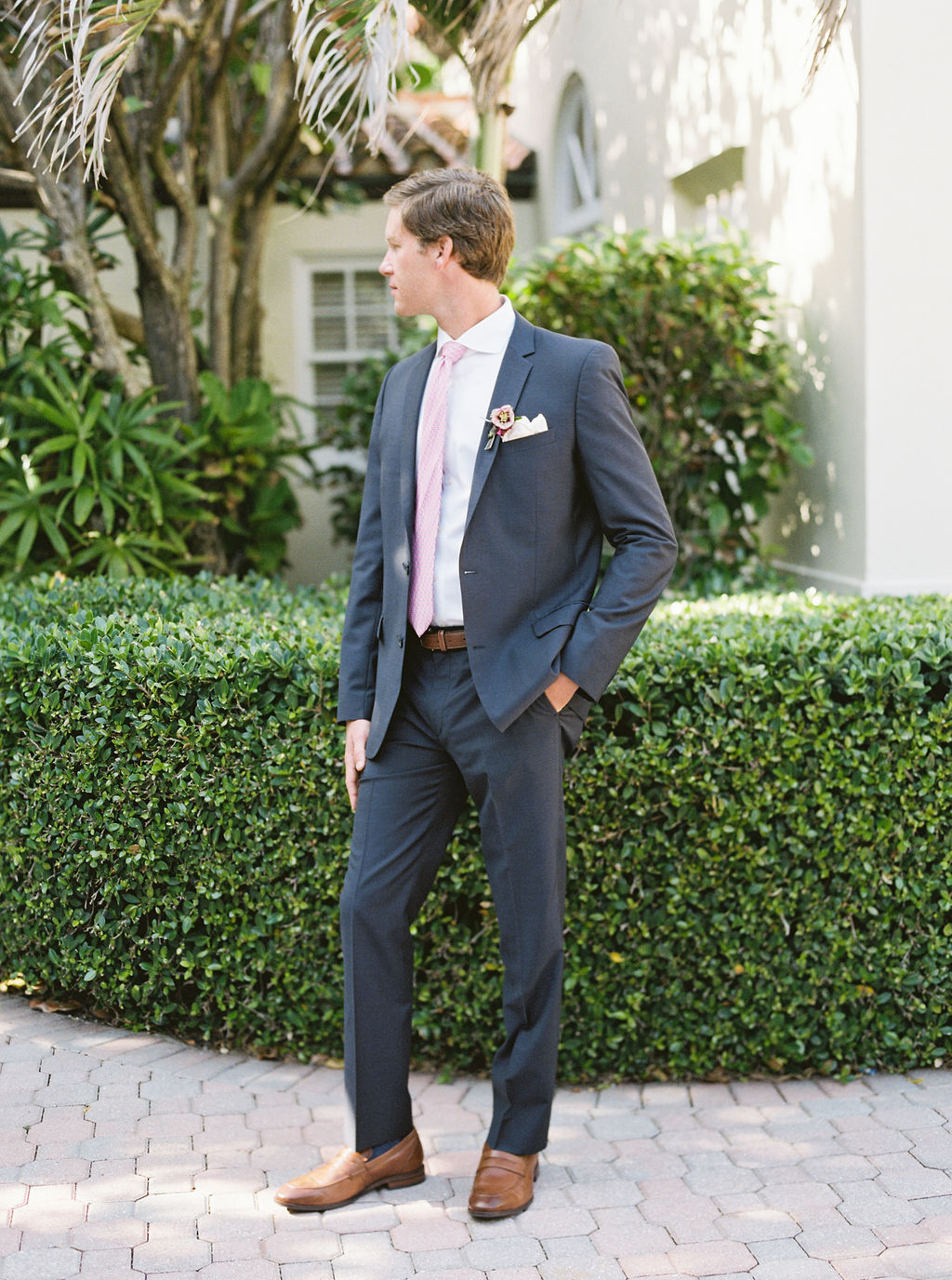 groom in blue suit and pink tie on patio