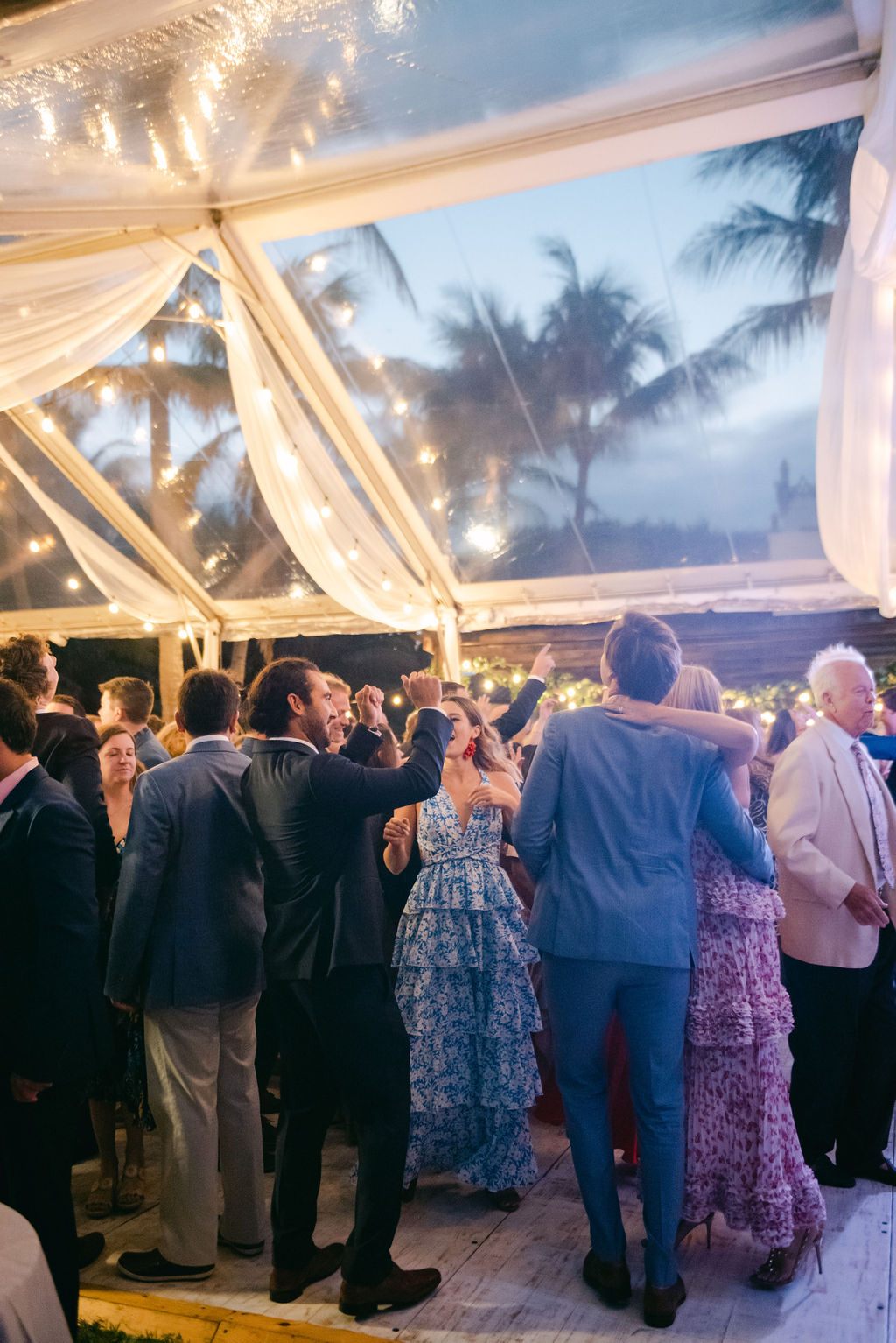 guests dancing under lit wedding tent at reception