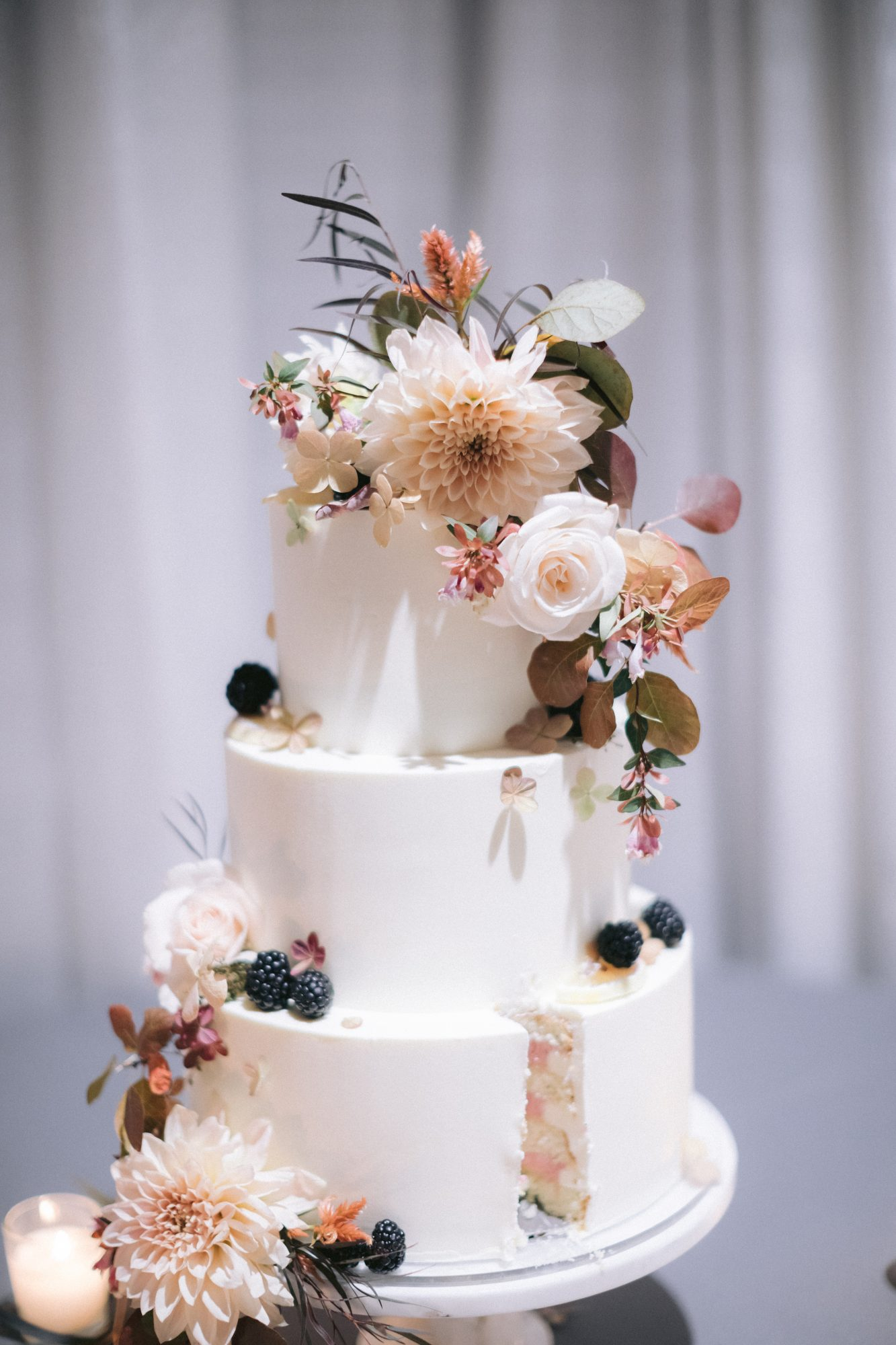 wedding cake covered in fall flowers