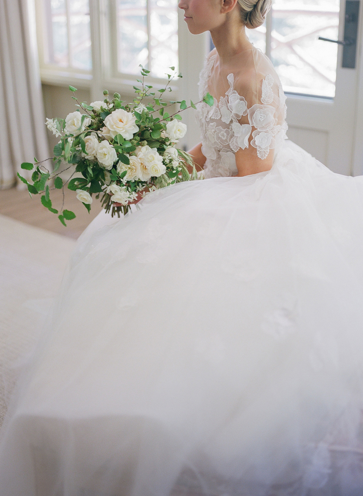 bride in fluffy dress sitting with bouquet