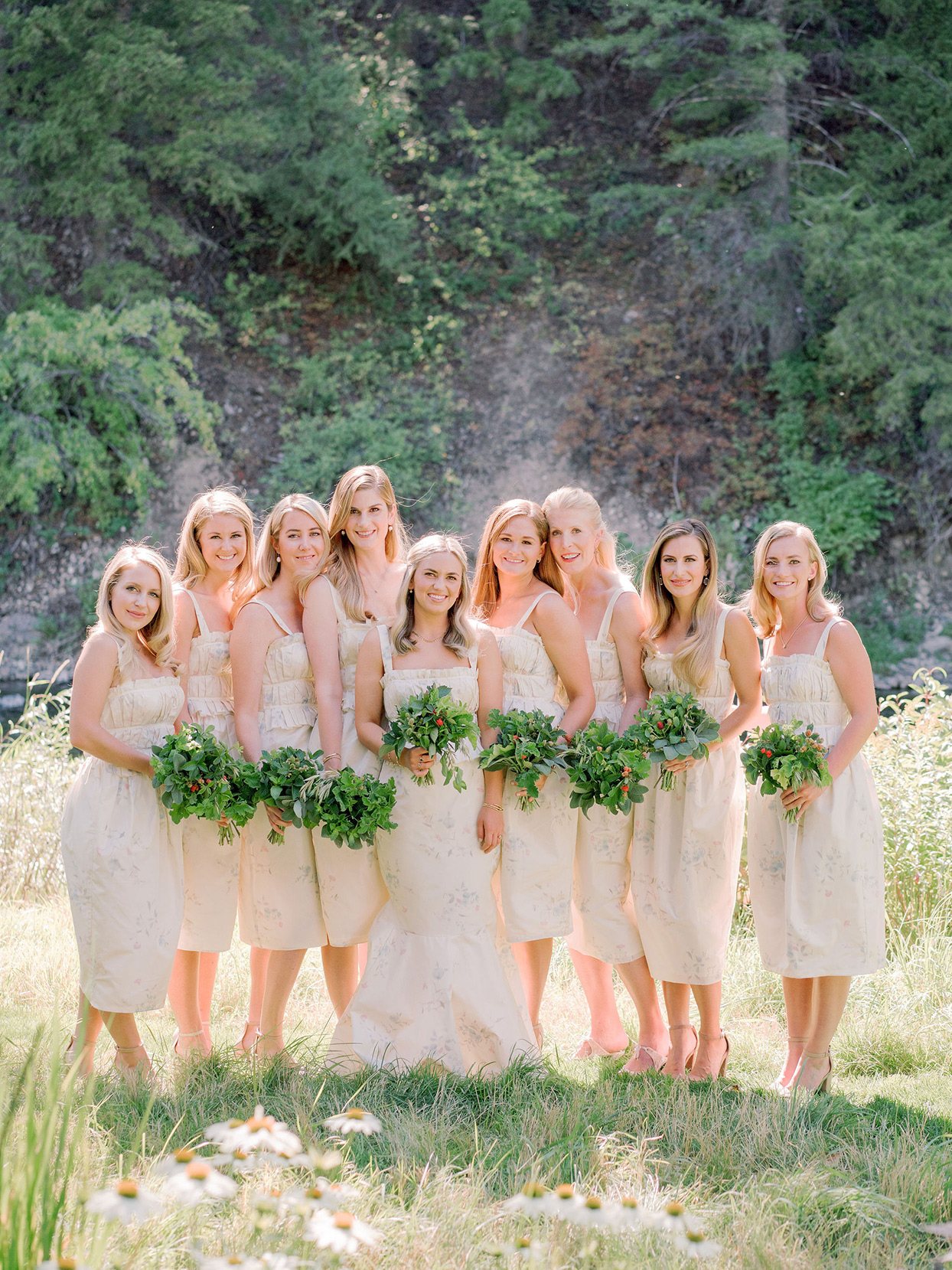 bridesmaids in muted floral print dresses standing in grassy field