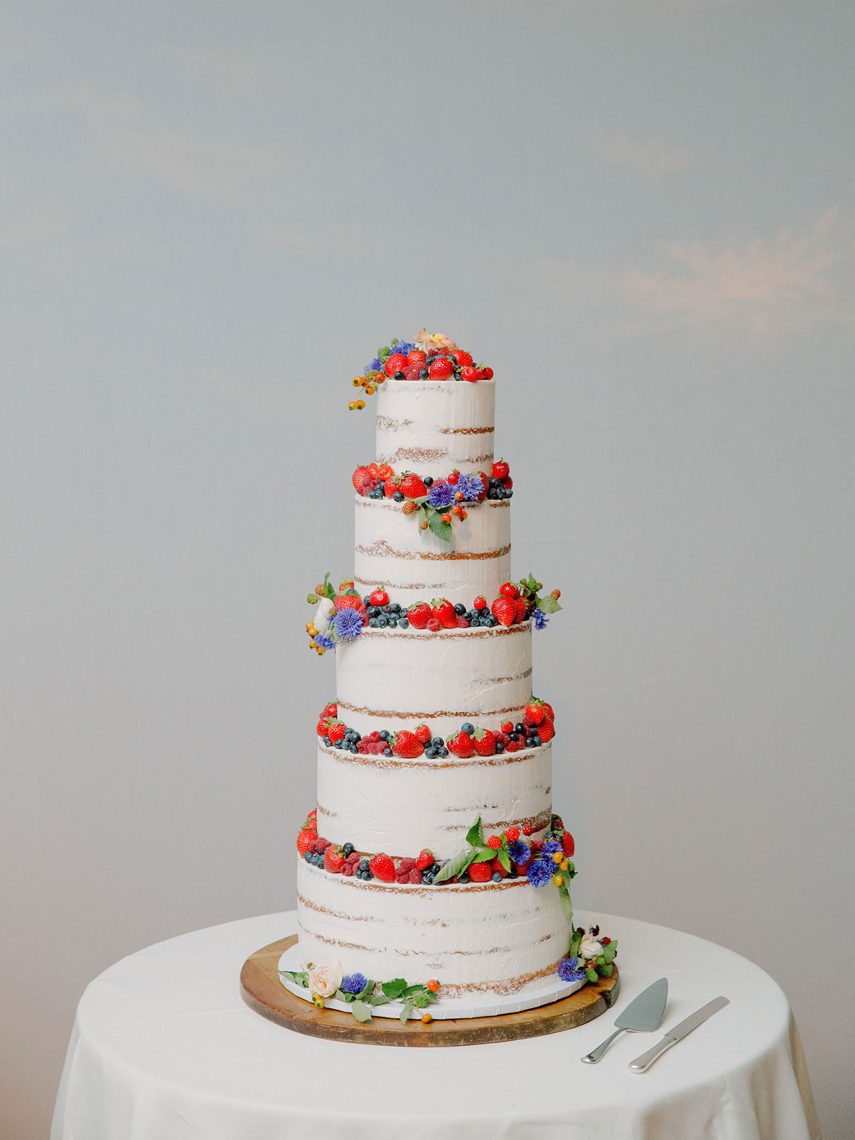 tall wedding cake with berry and wildflower decorations