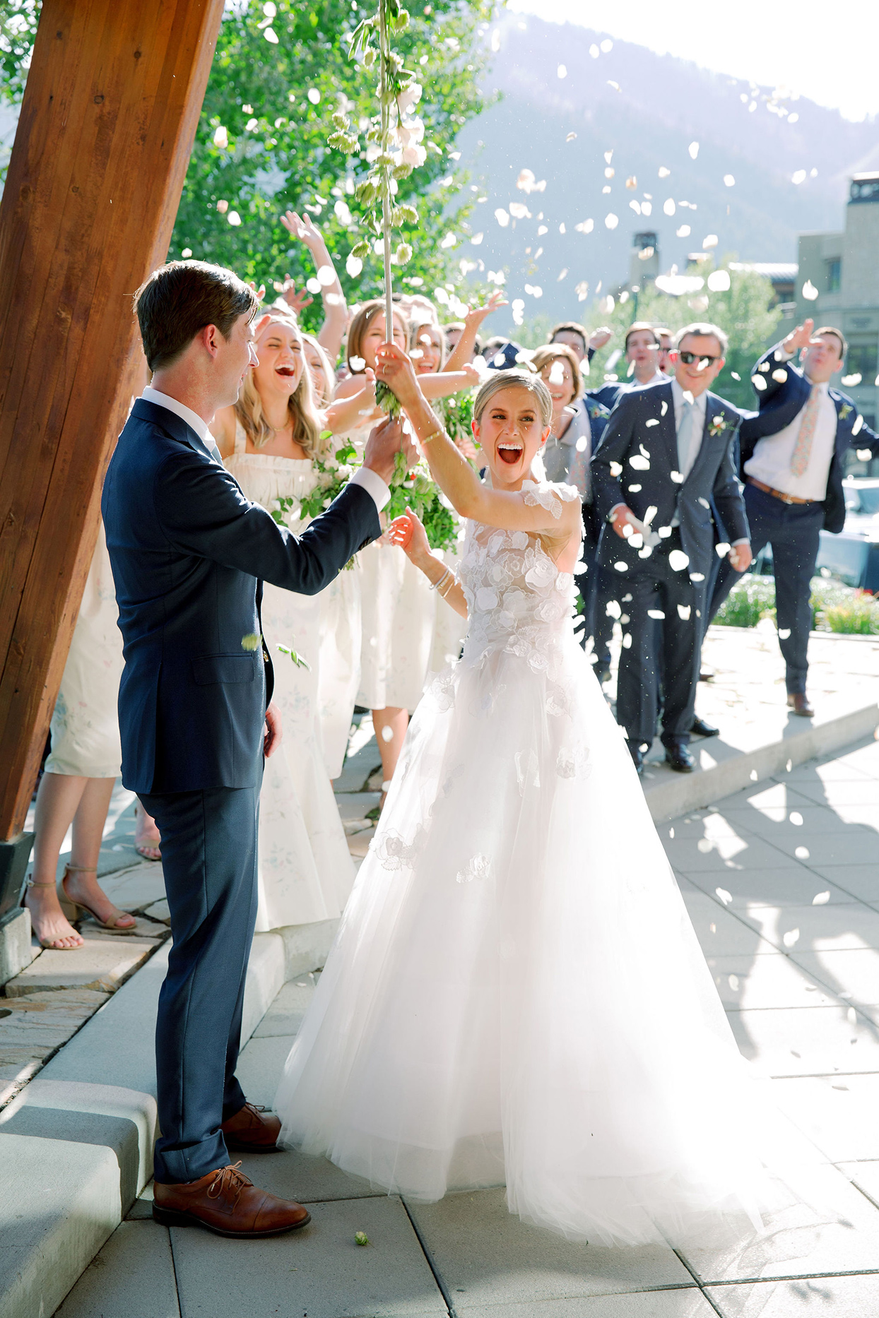 couple ringing bell after ceremony while being showered in flower petals
