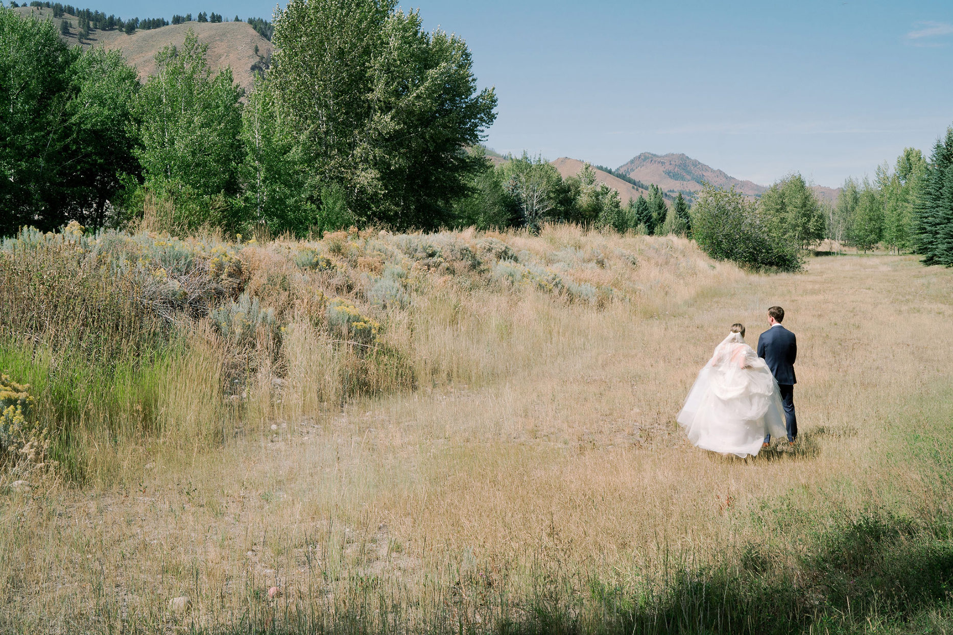 wedding couple first look in field with mountain view