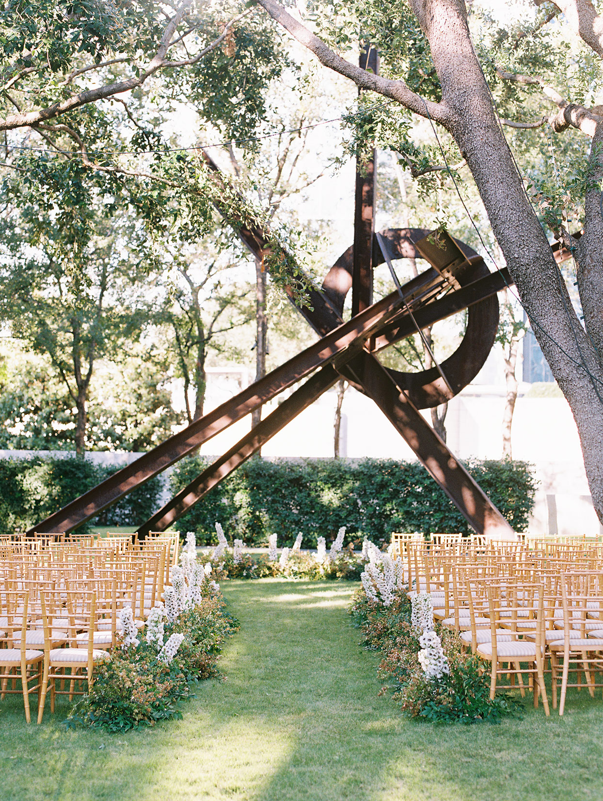 outdoor ceremony space with gold chairs and central modern art sculpture