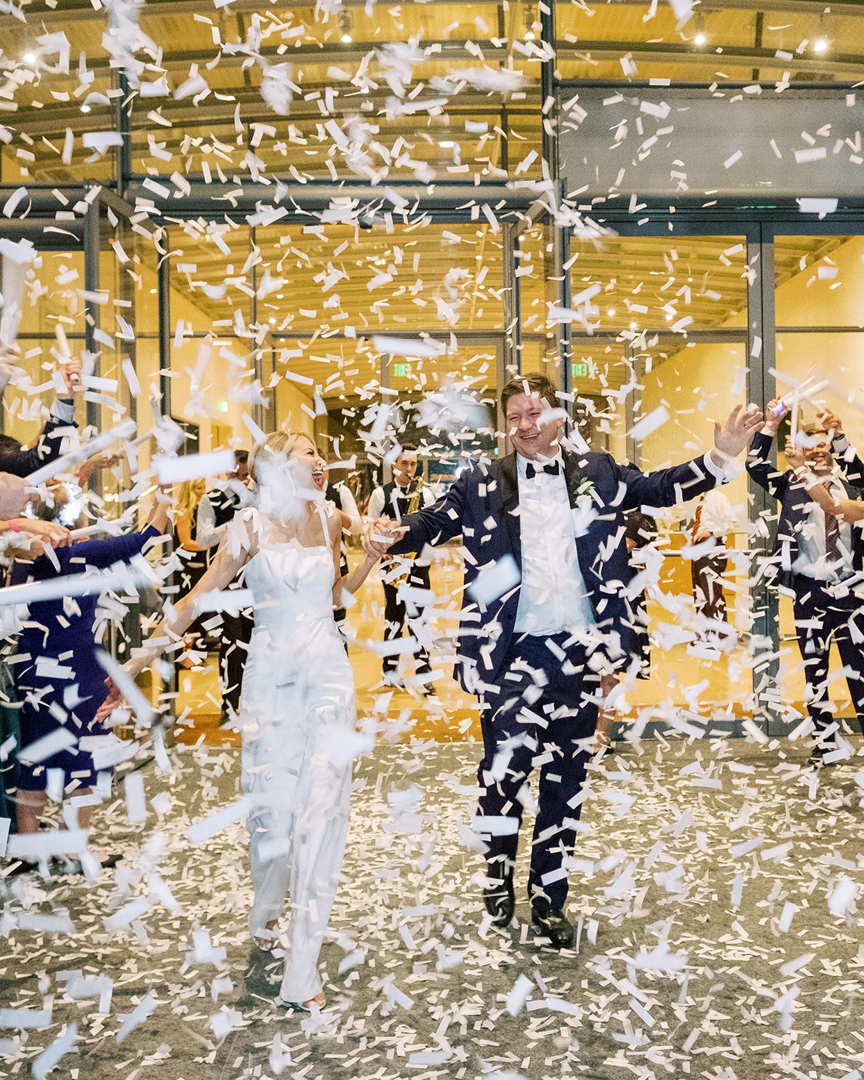bride and groom exiting wedding showered in confetti