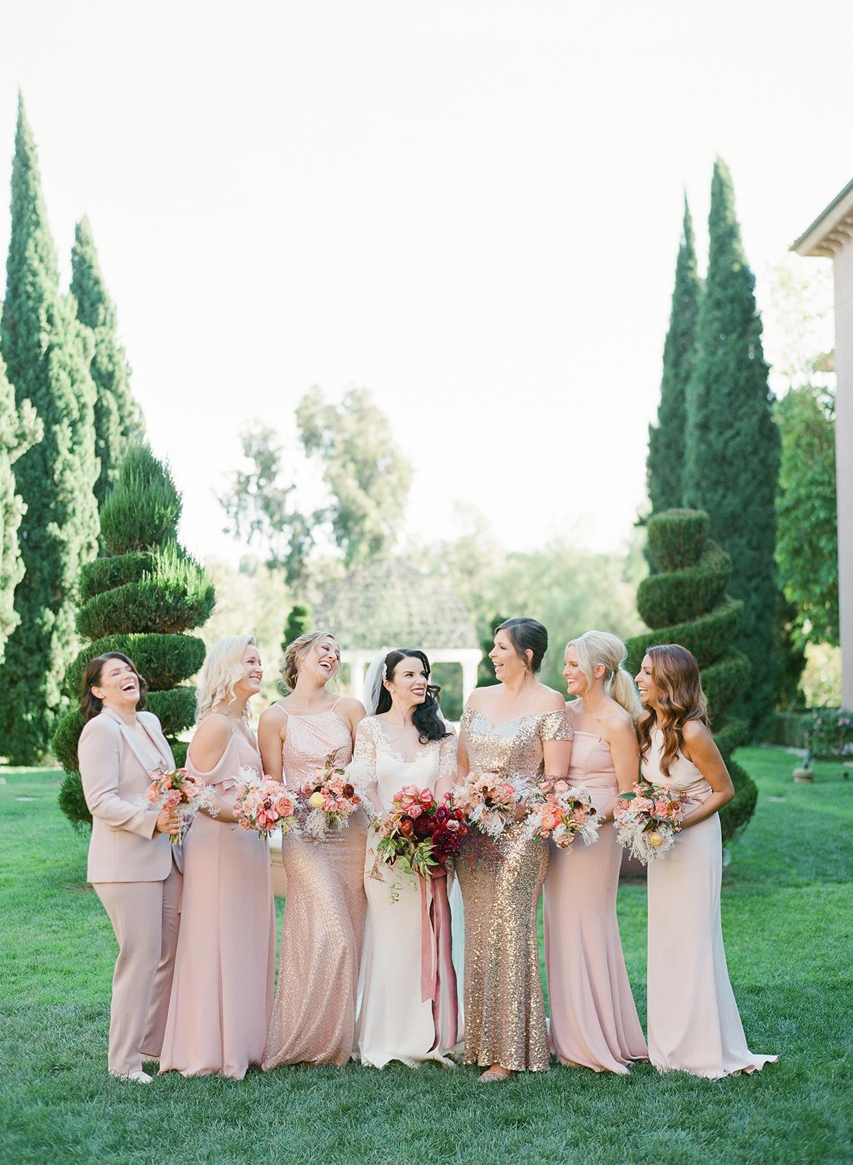 bride and bridesmaids standing in garden in pastel pink dresses