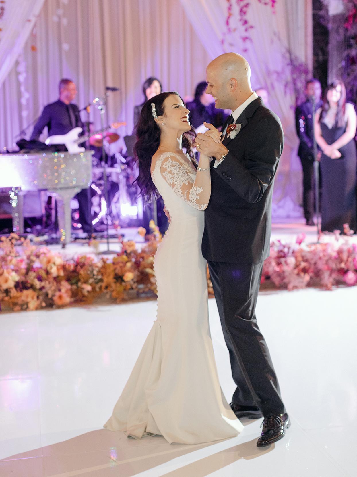 wedding couple first dance in ballroom under purple lights
