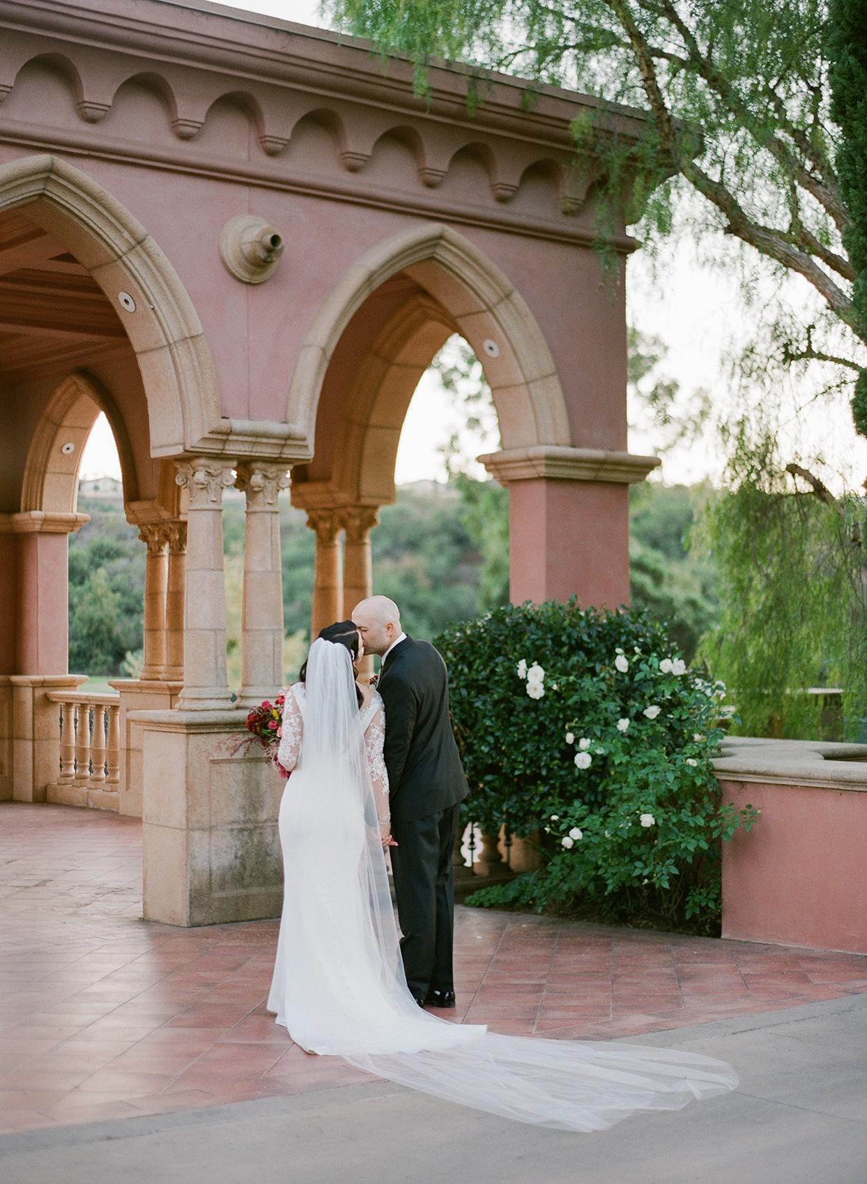wedding couple kissing on hotel patio