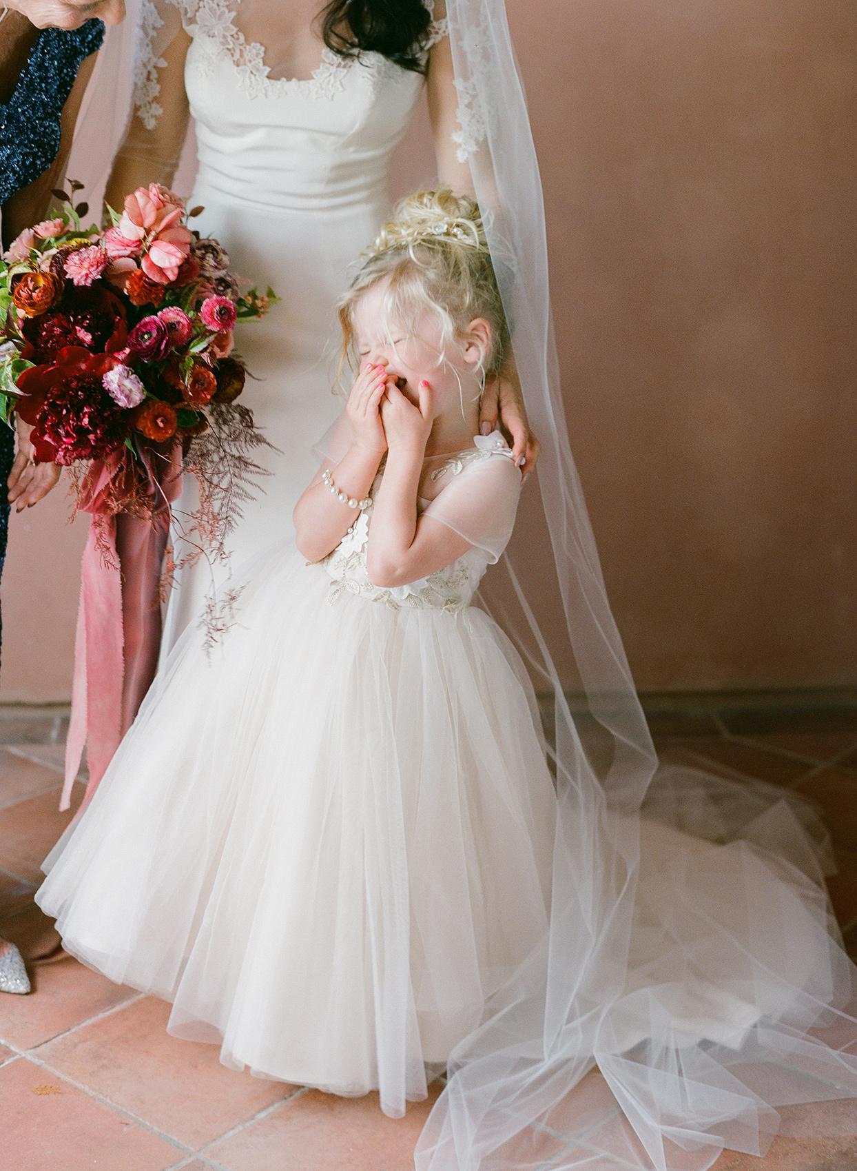 flower girl laughing in white tulle dress