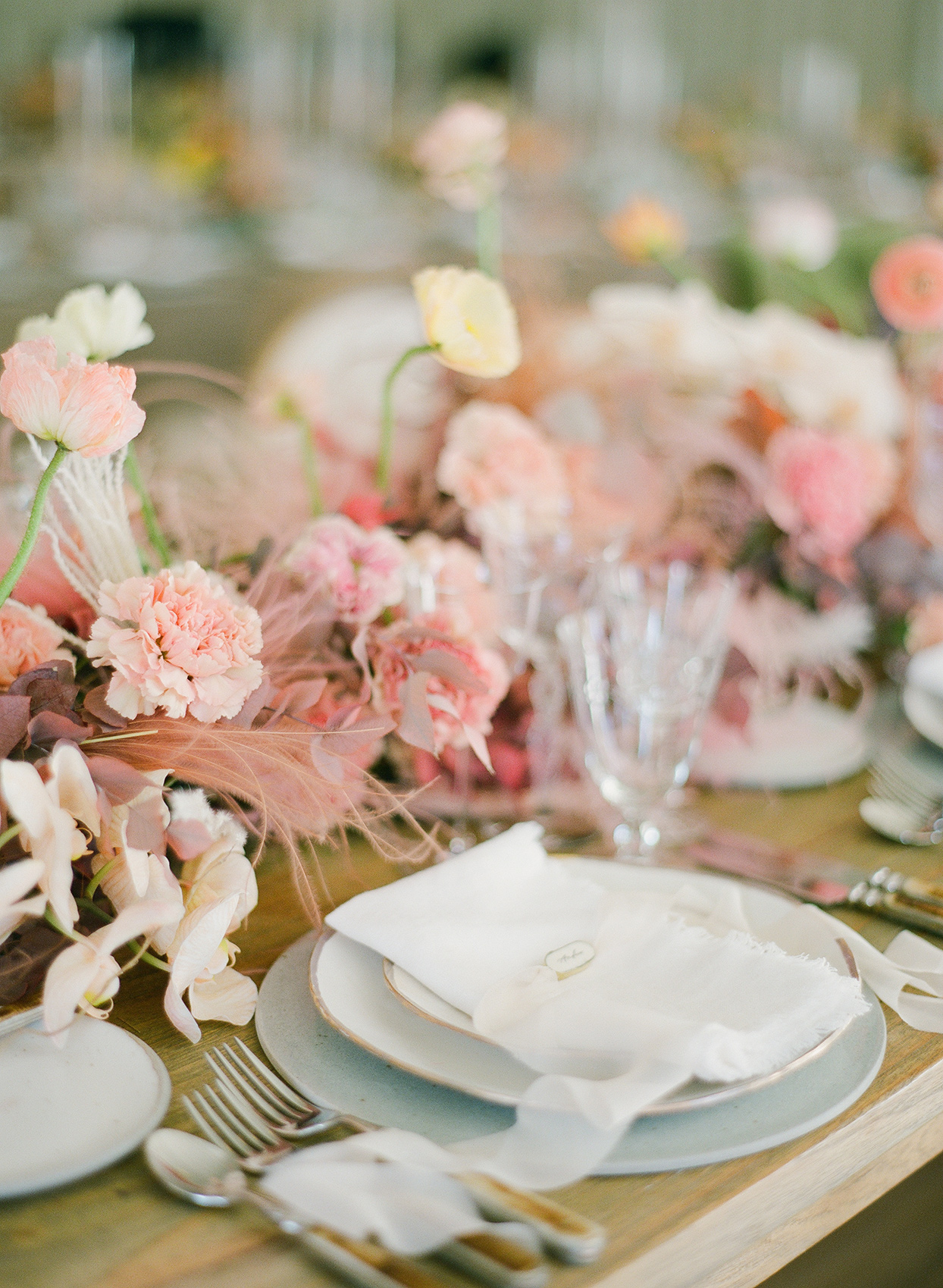 elegant wooden table reception place setting with floral and feather centerpieces