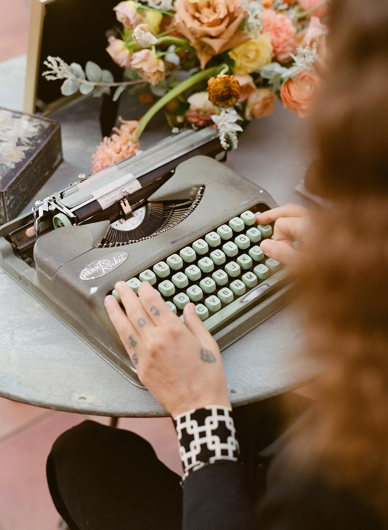 guest typing on wedding typewriter
