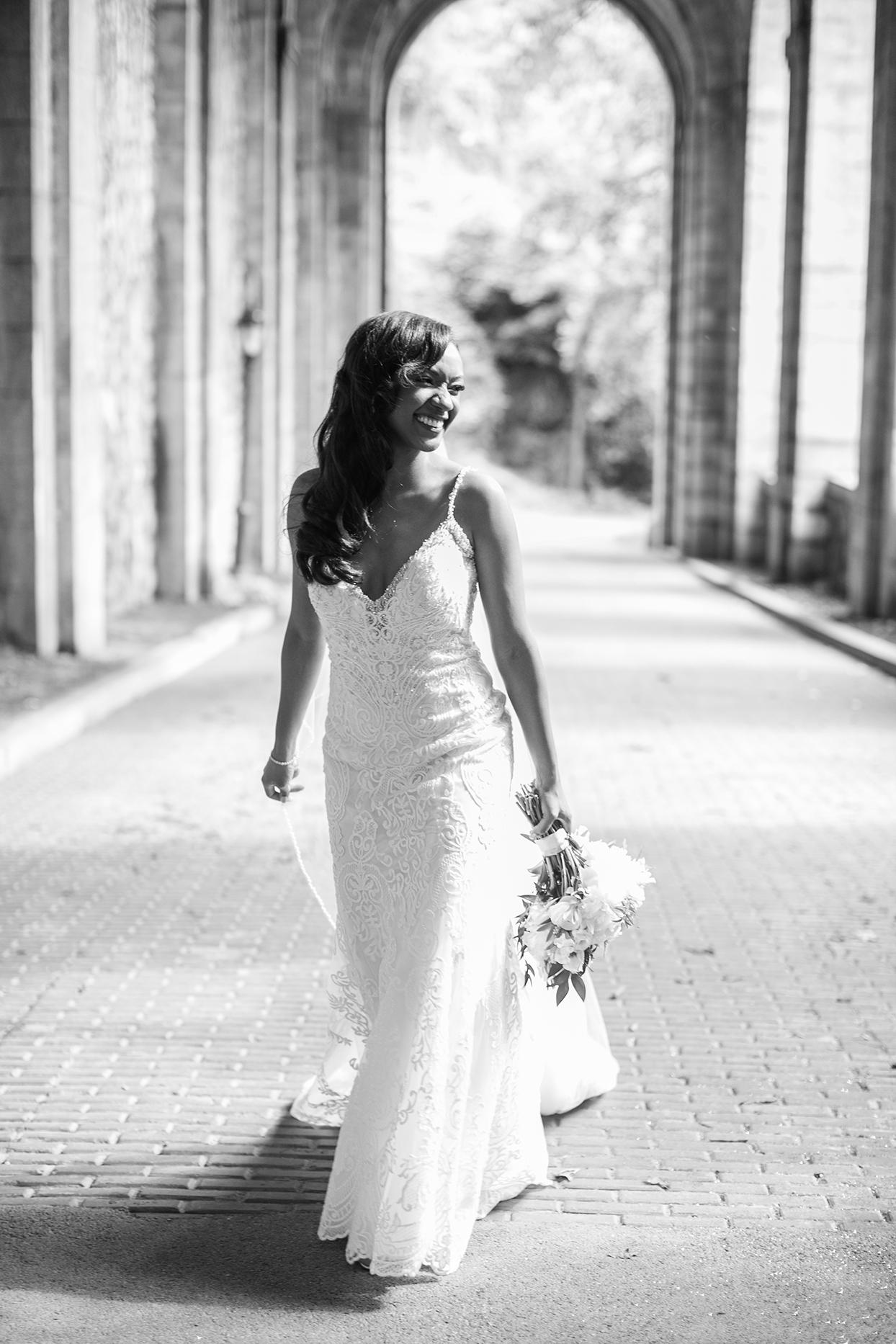 bride in lace dress walking through park columns