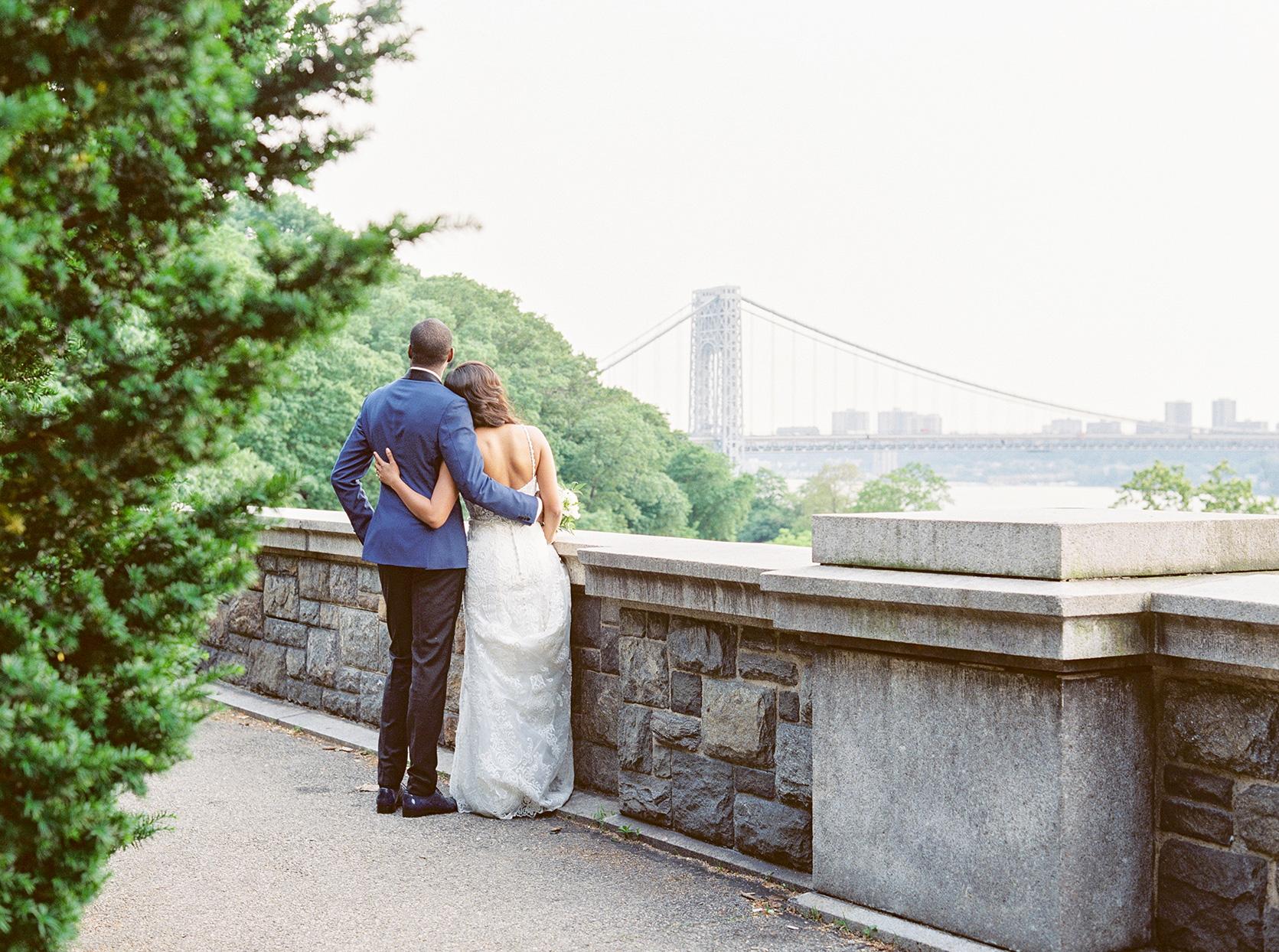 wedding couple standing on edge of park overlooking george washington bridge