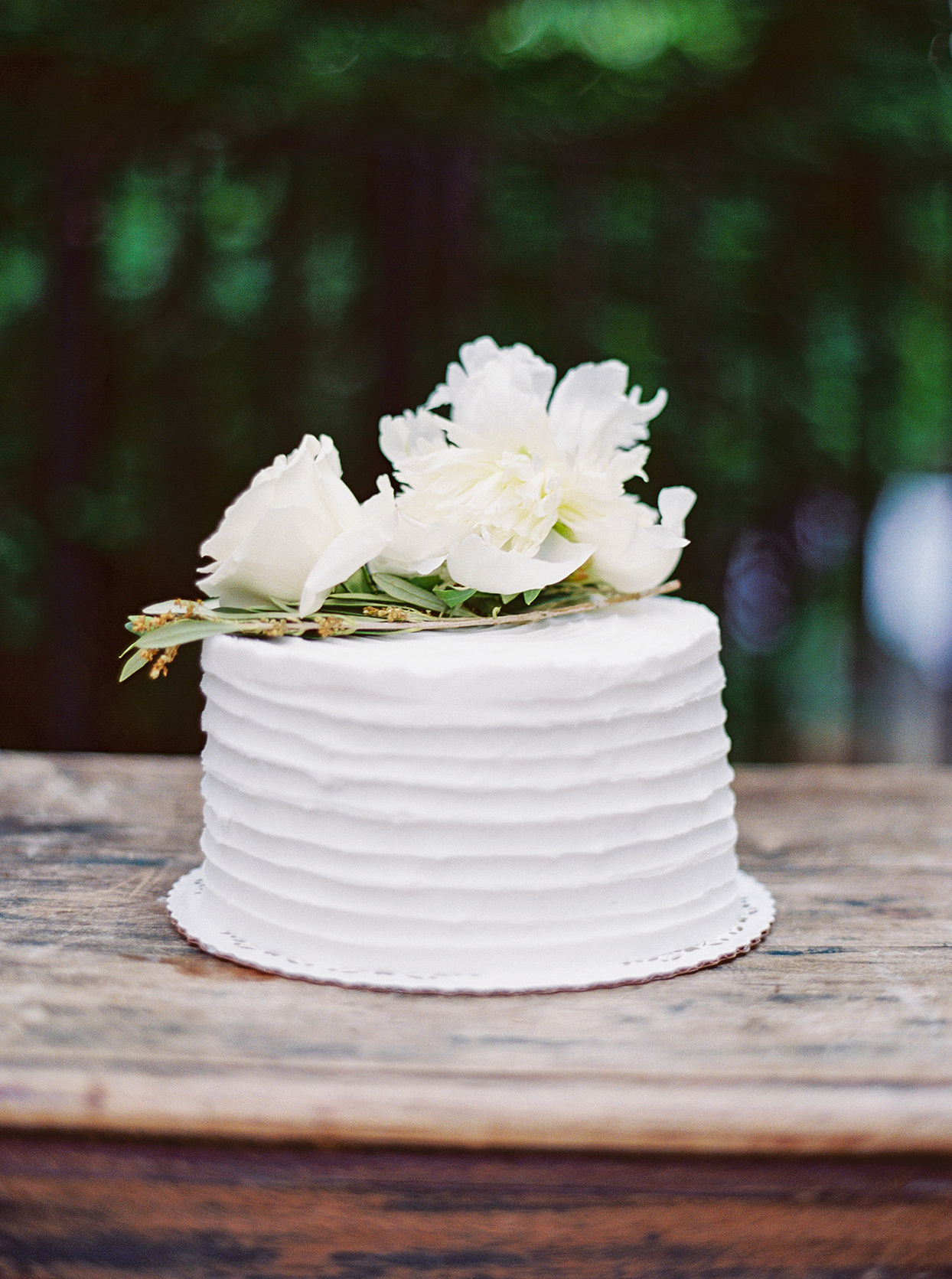simple white wedding cake with florals on wooden table