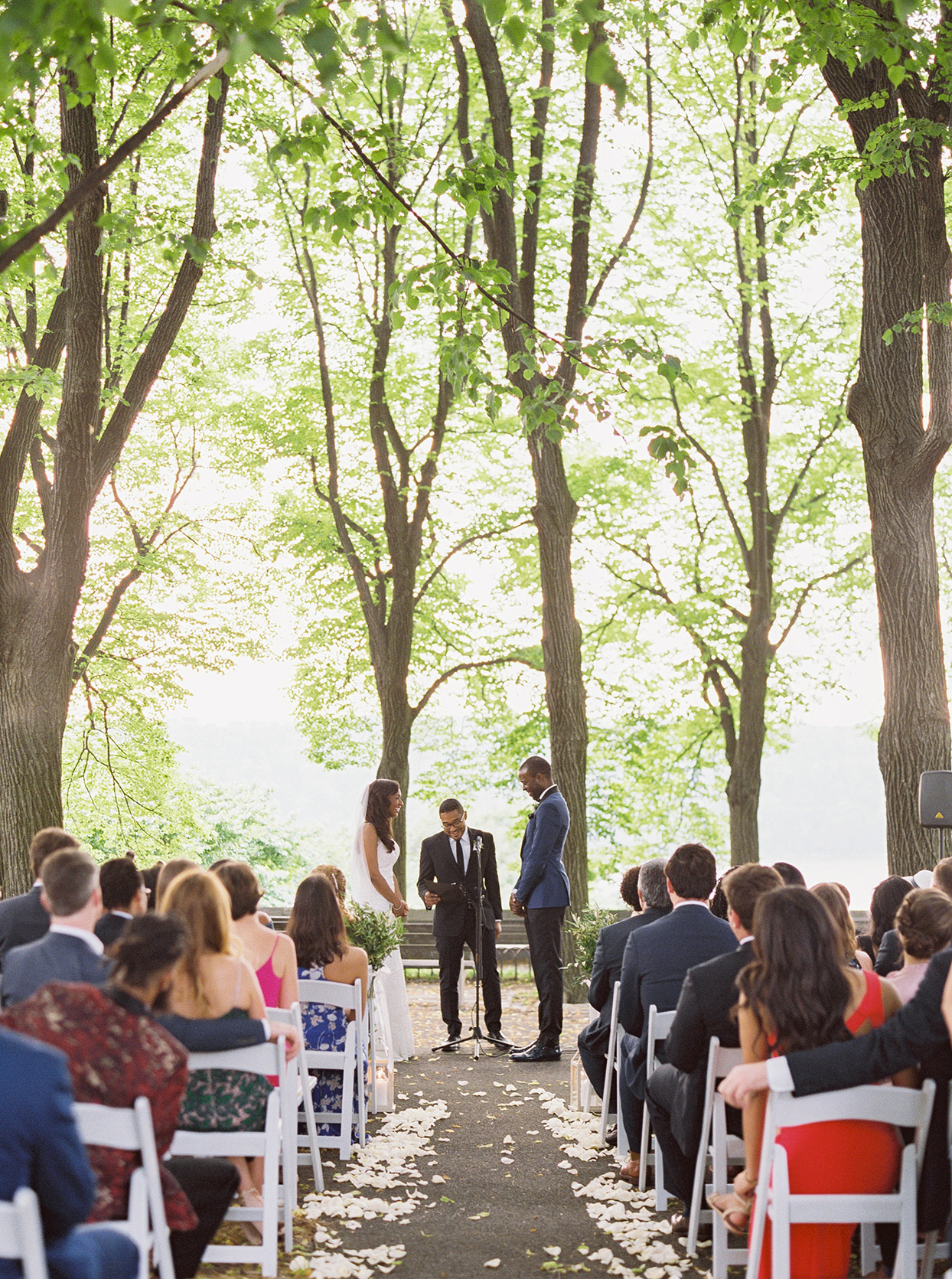 outdoor woodsy wedding ceremony couple smiling with officiant