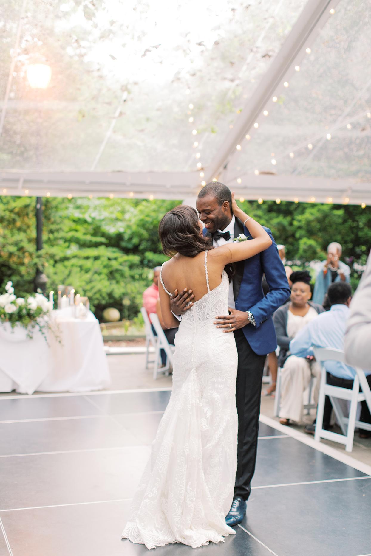 wedding couple first dance on outdoor dance floor under tent