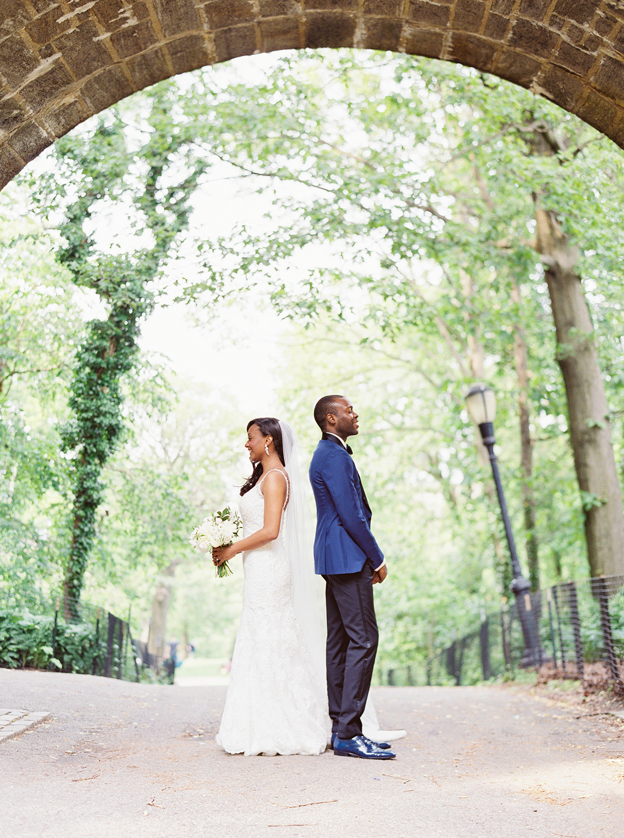 bride and groom standing back to back in park for first look