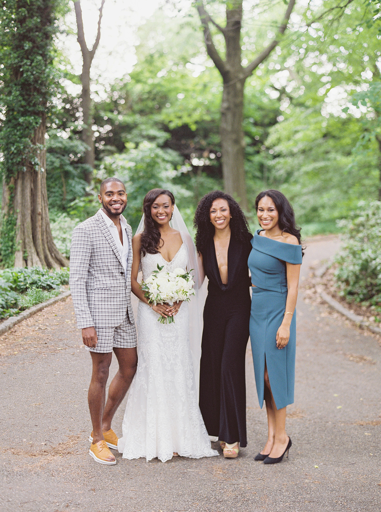 bride and friends standing on park path