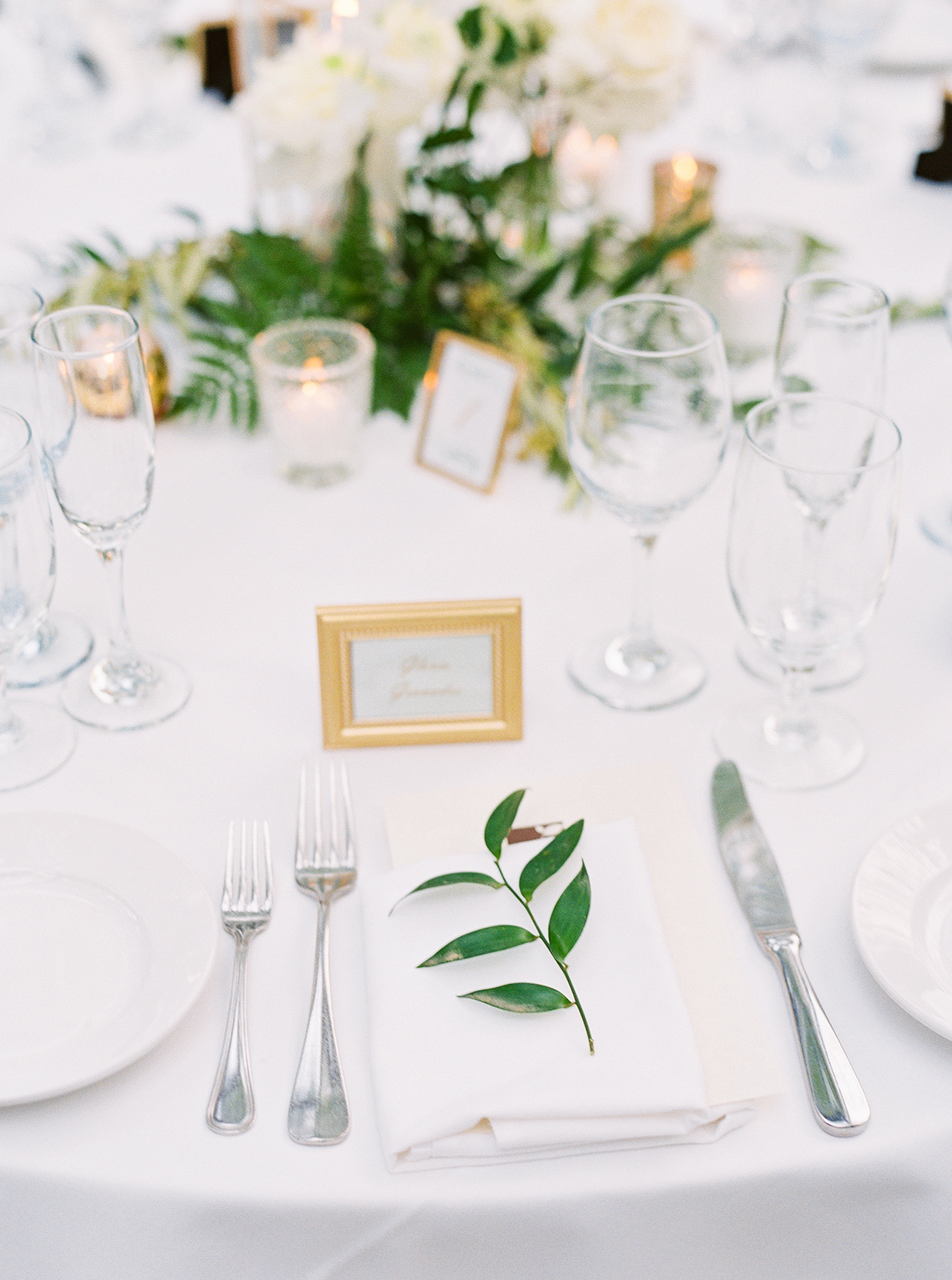 simple elegant white place setting with greenery