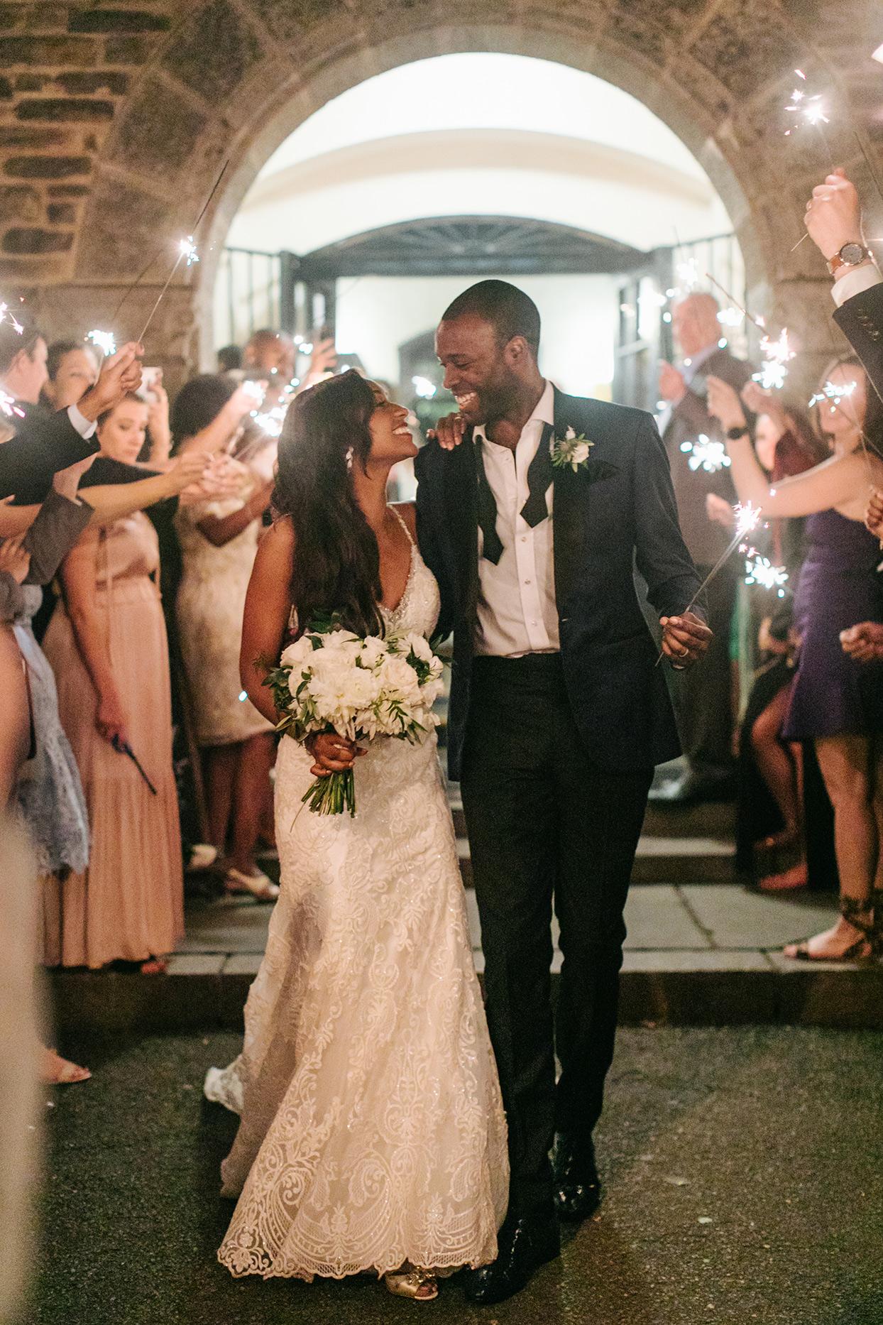 bride and groom exiting wedding reception under sparklers