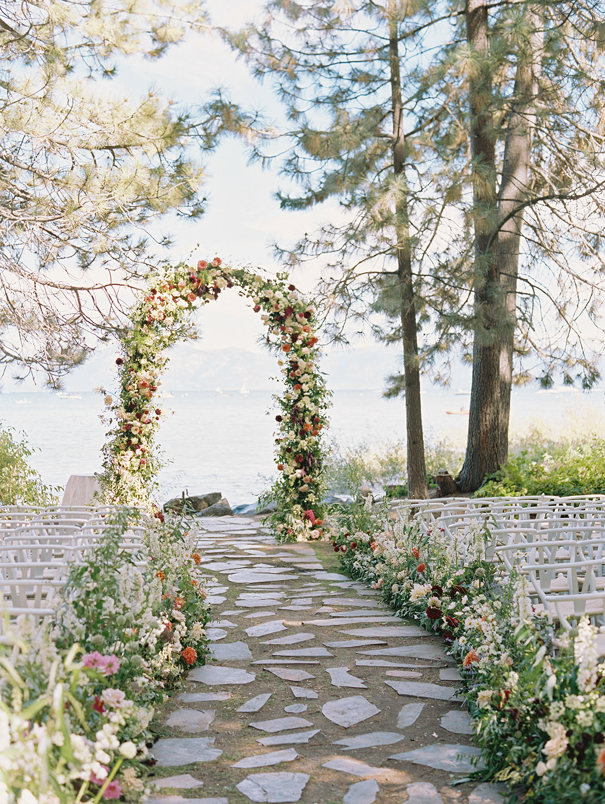 outdoor wedding ceremony location with wildflower arch overlooking lake